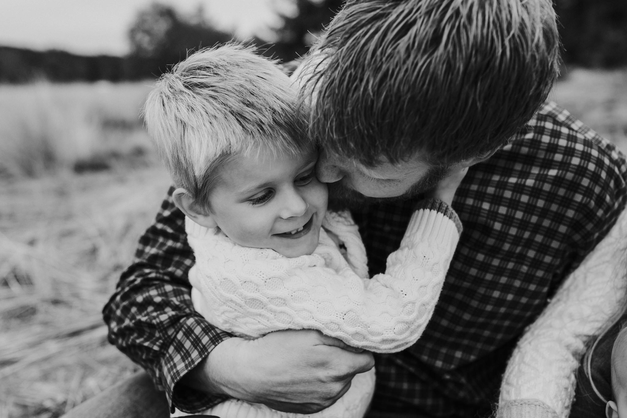 kara chappell whidbey island family photography dad snuggles son on blanket at park