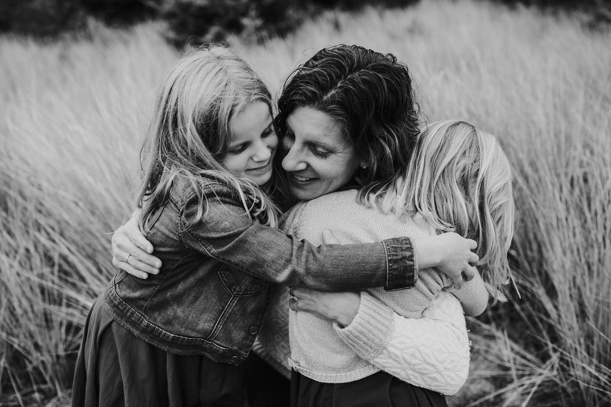 kara chappell whidbey island family photography mom snuggles daughters in field