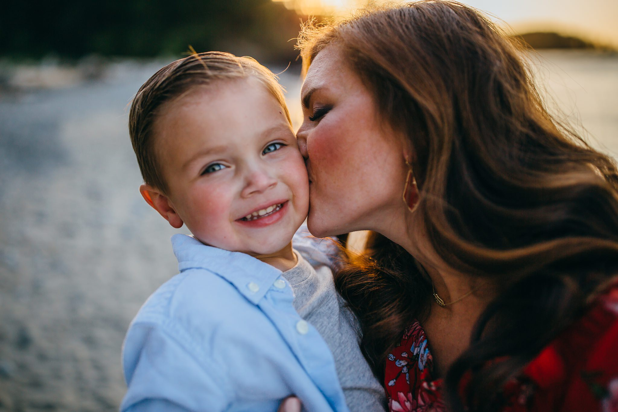 Mom kisses on on cheek on beach | Whidbey Island Family Photographer