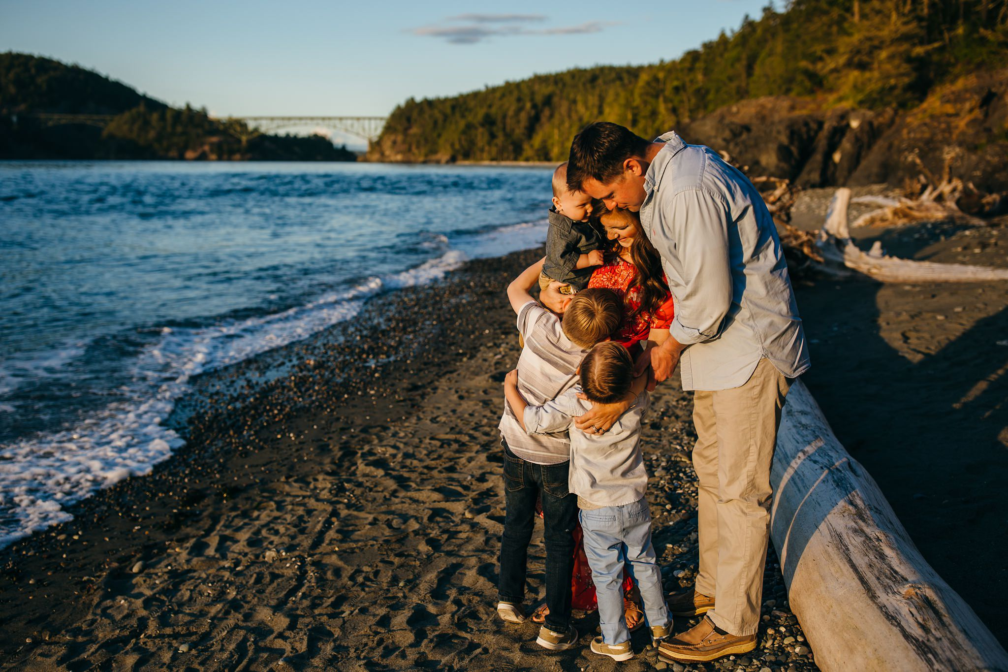 Family hugs on beach with Deception Pass bridge in background