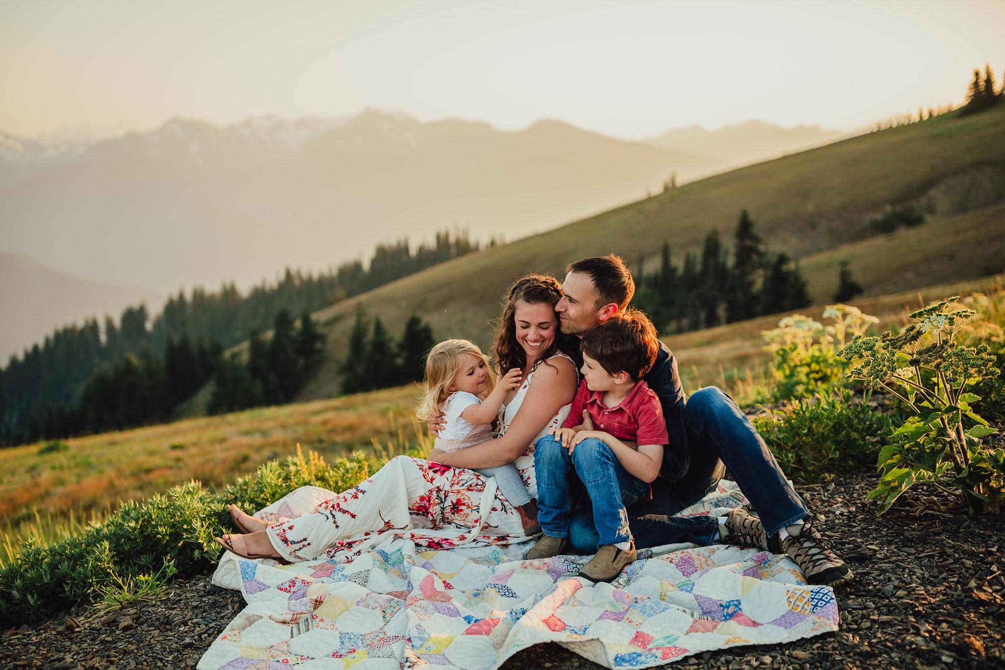 family sits on blankets at hurricane ridge