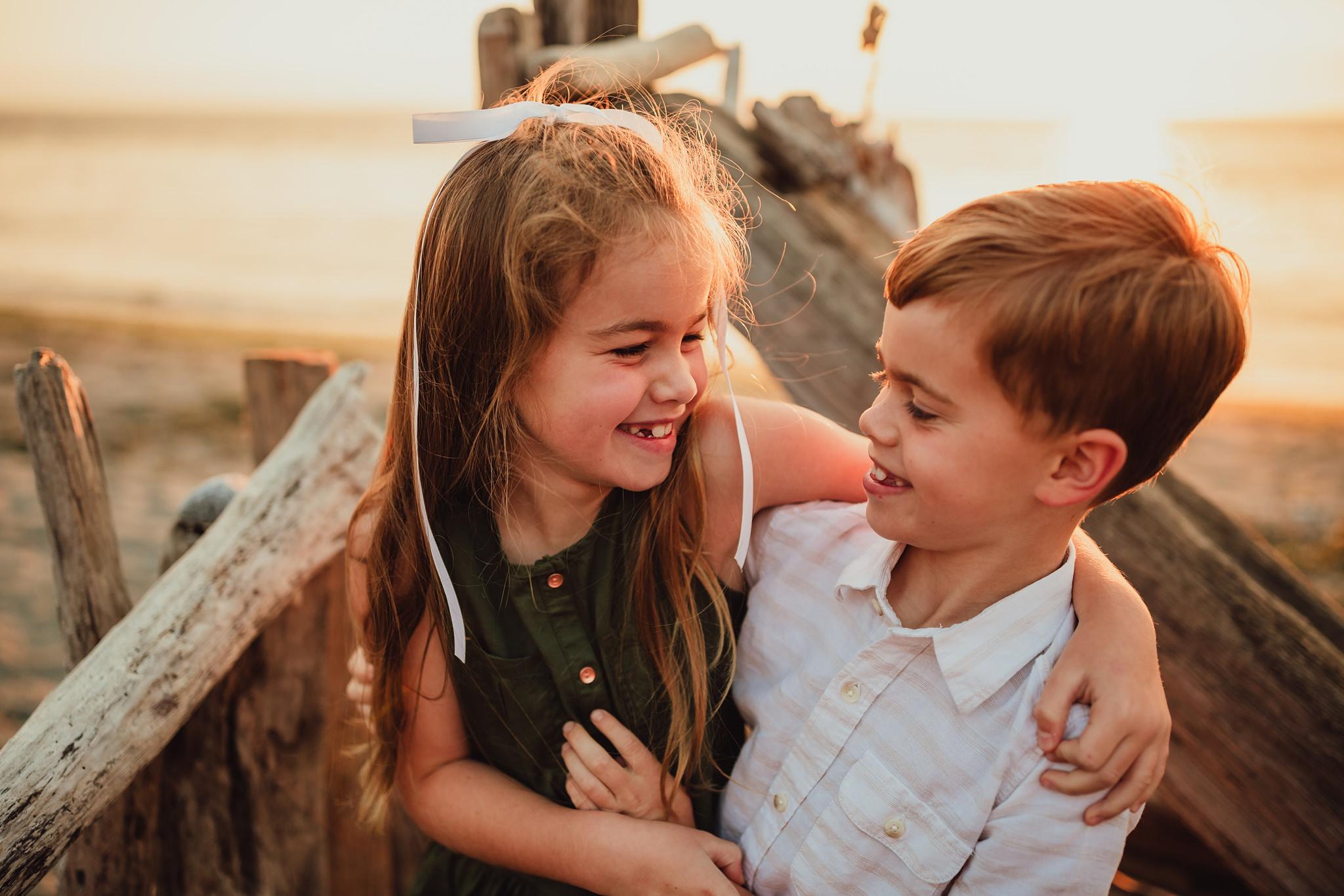 kids hug during family photo session on Washington beach