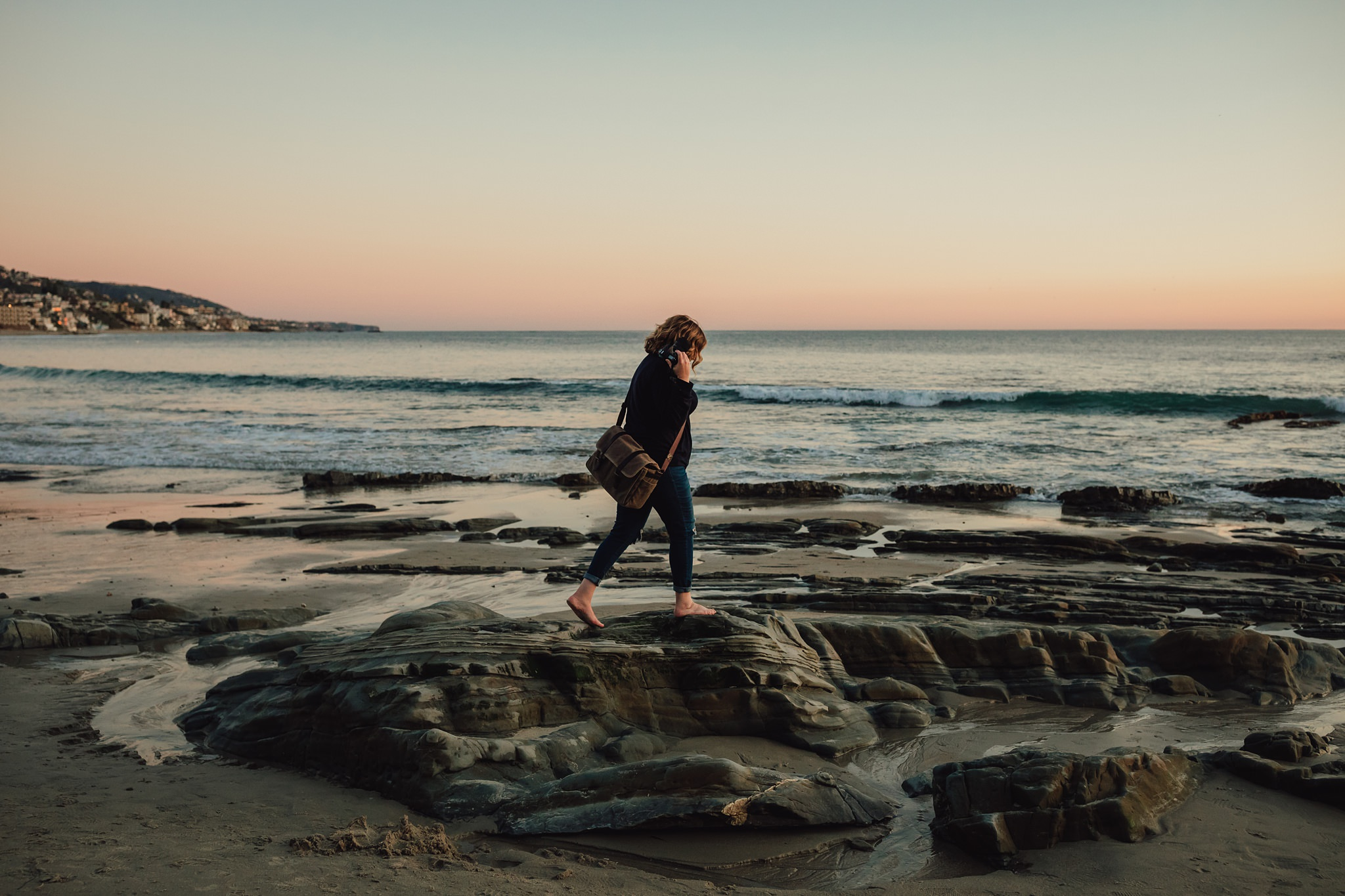 woman walks on rocks at Laguna Beach | Whidbey Island family photographer