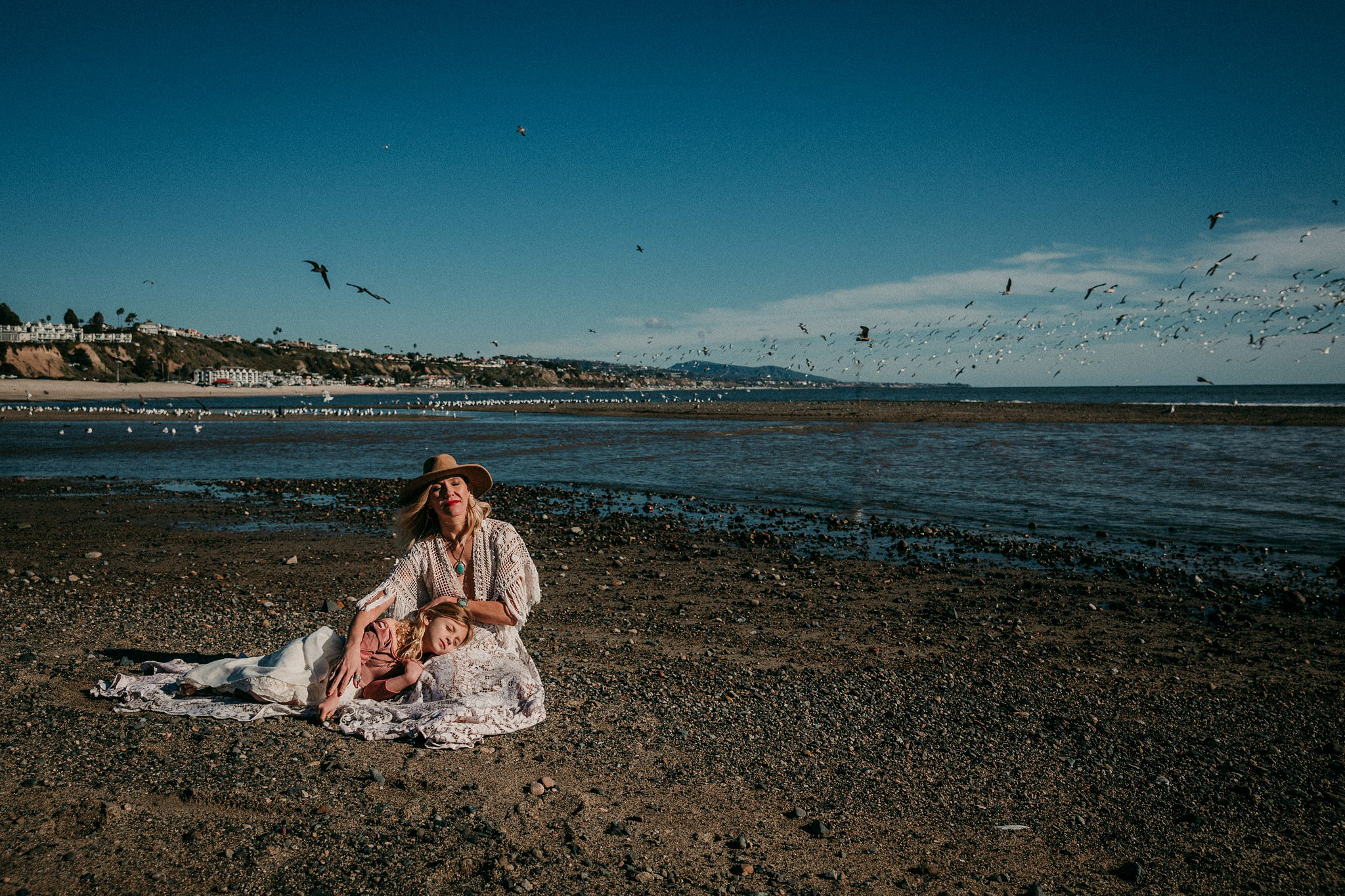 woman and daughter sit on Laguna Beach midday | Whidbey Island family photographer