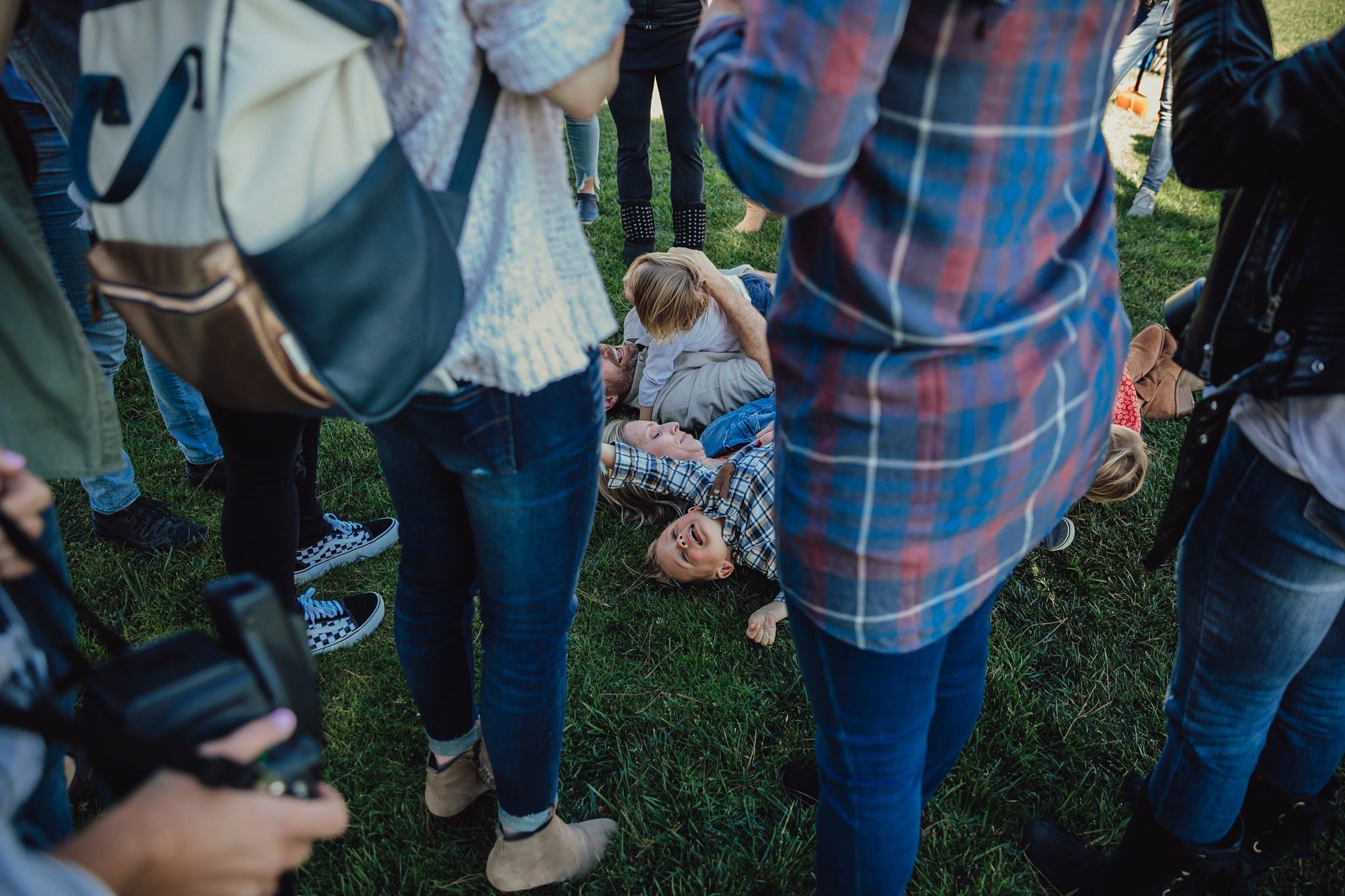 photographers crowd around family playing on grass | Whidbey Island family photographer