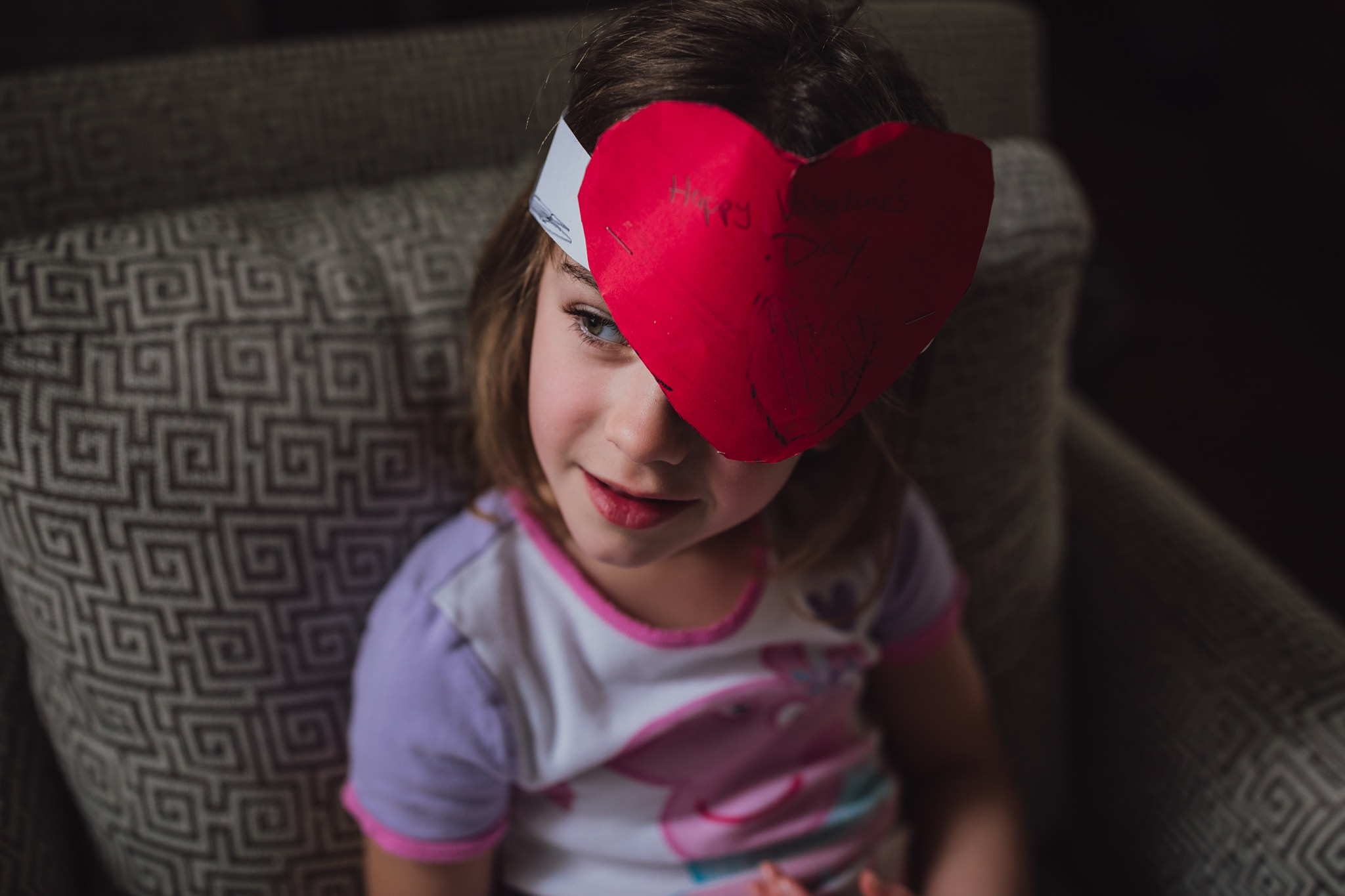 girl looks out window with Valentine's hat on | Whidbey Island family photographer