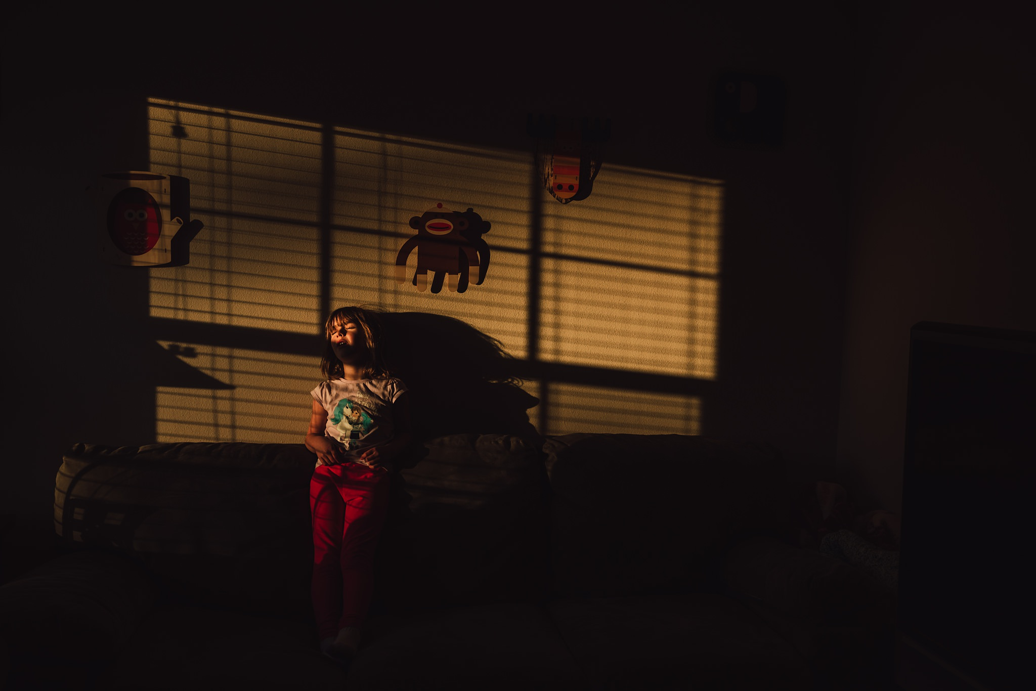 girl stands on couch in harsh window light | Whidbey Island family photographer