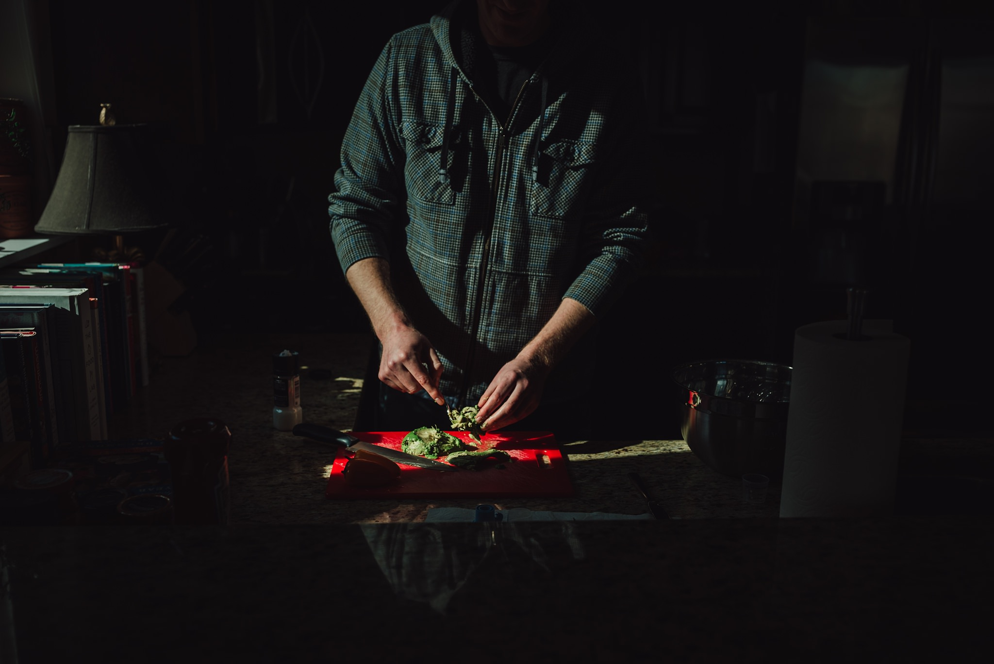 man cuts vegetables in kitchen while standing in harsh light | Whidbey Island family photographer