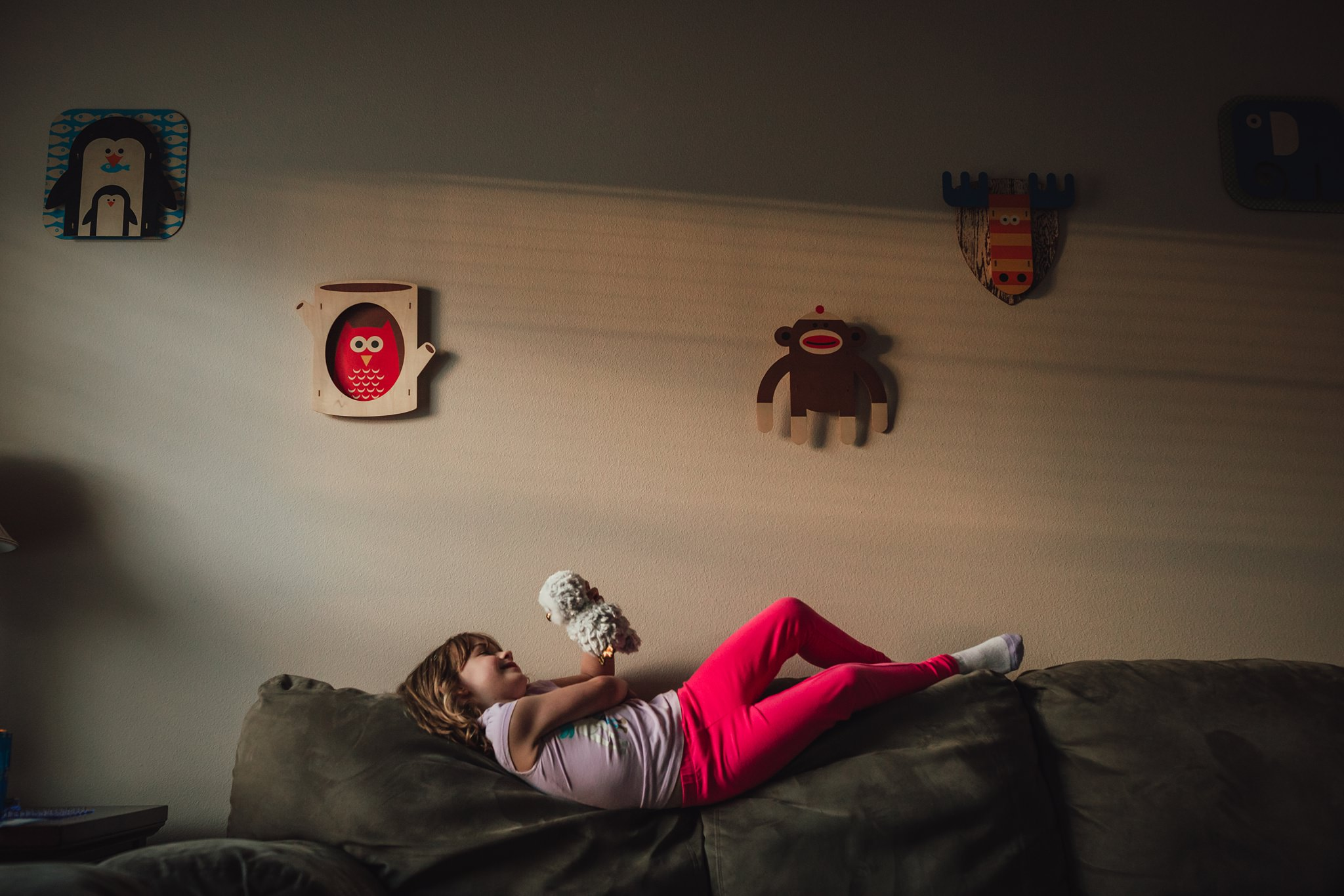 girl smiles at stuffed animal while lying on couch