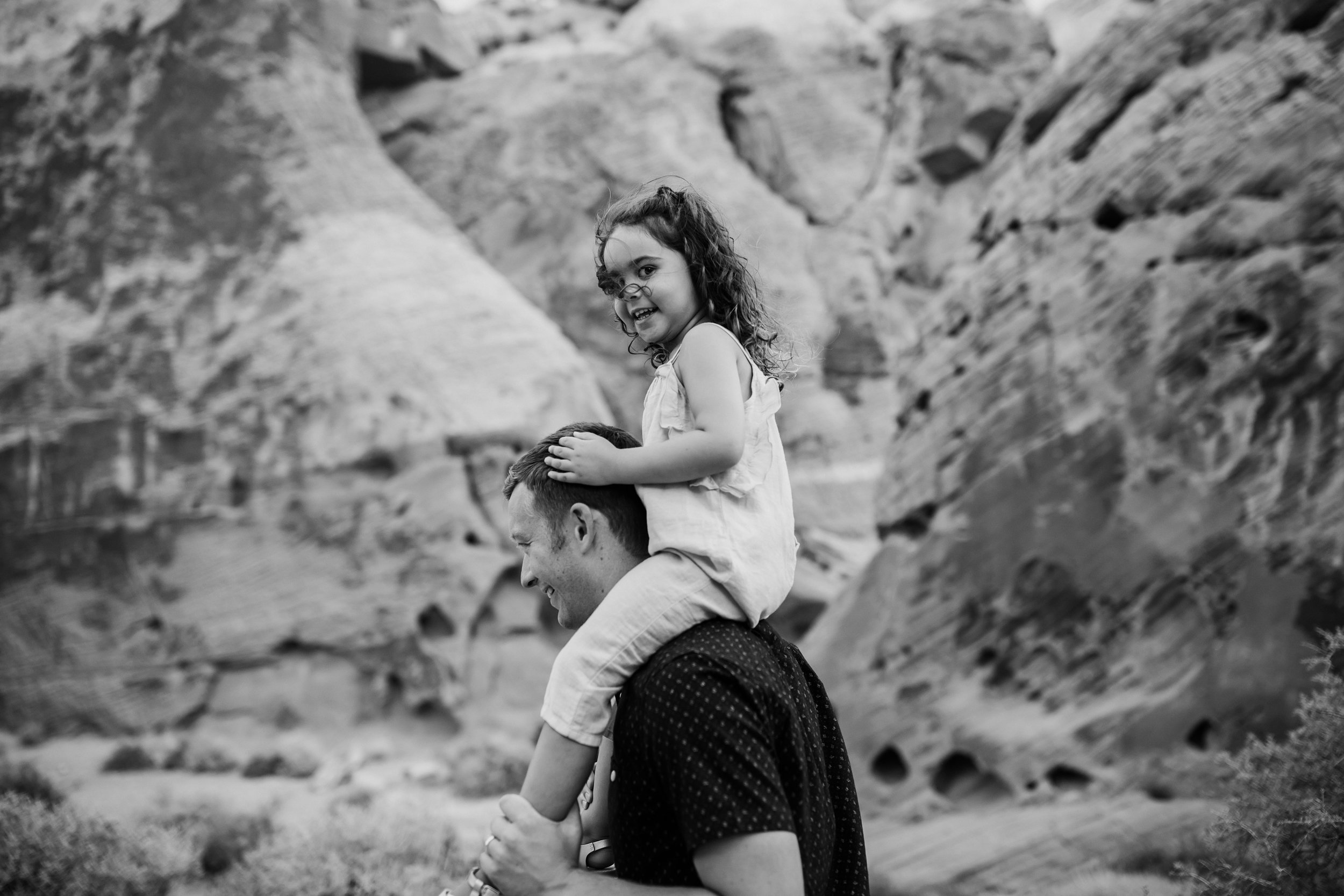 girl rides dad's shoulders during family pictures