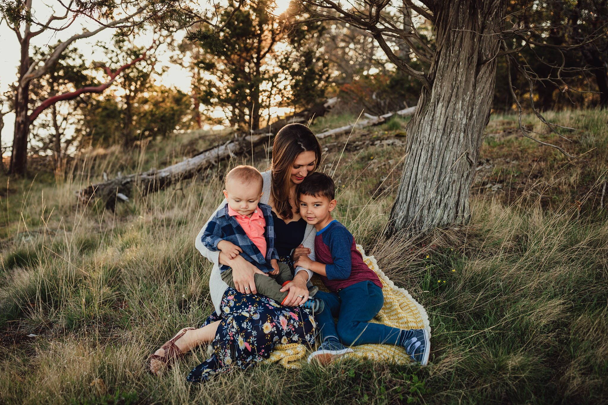 mother snuggles young sons at family photo session