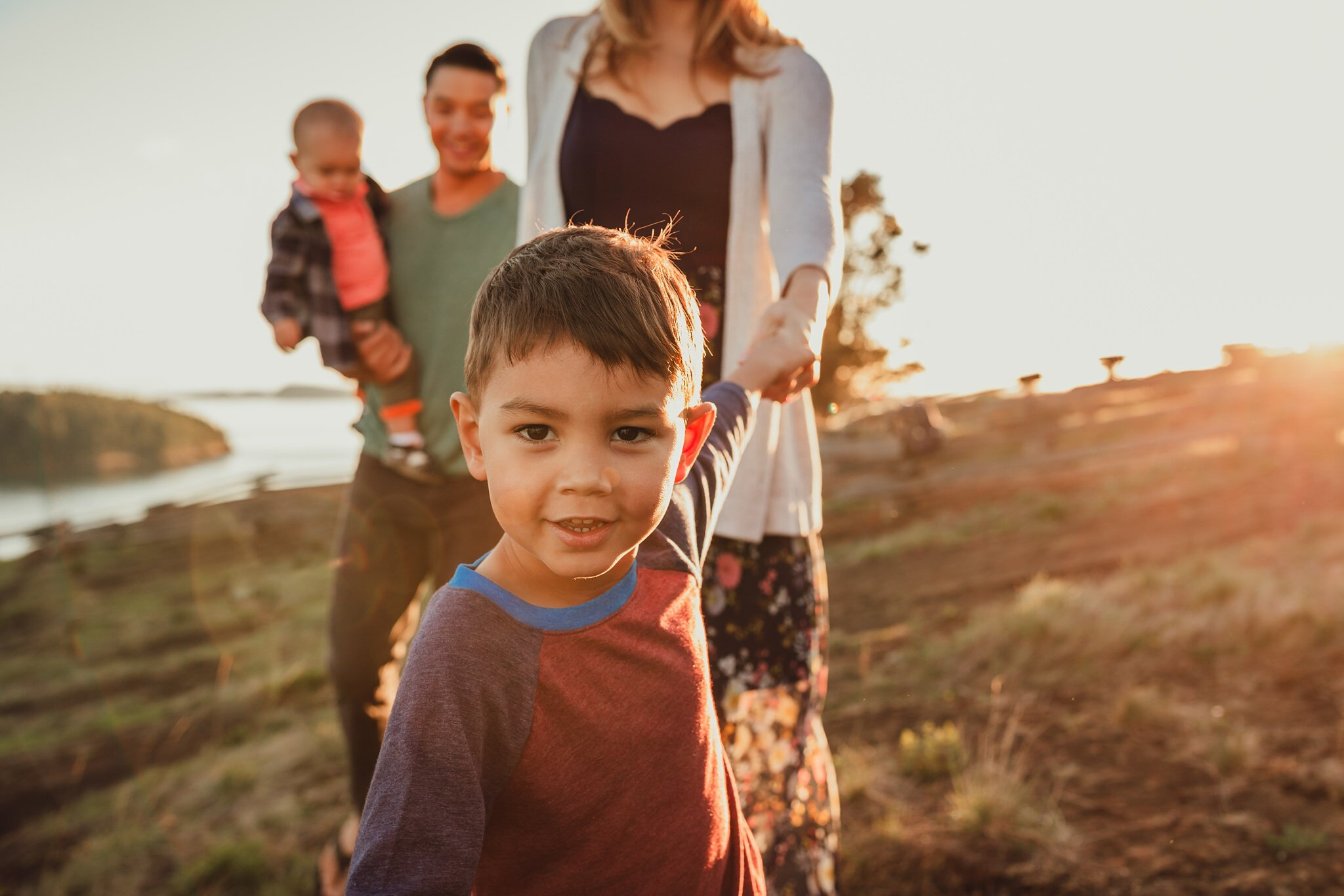 boy leads family on walk during photo shoot