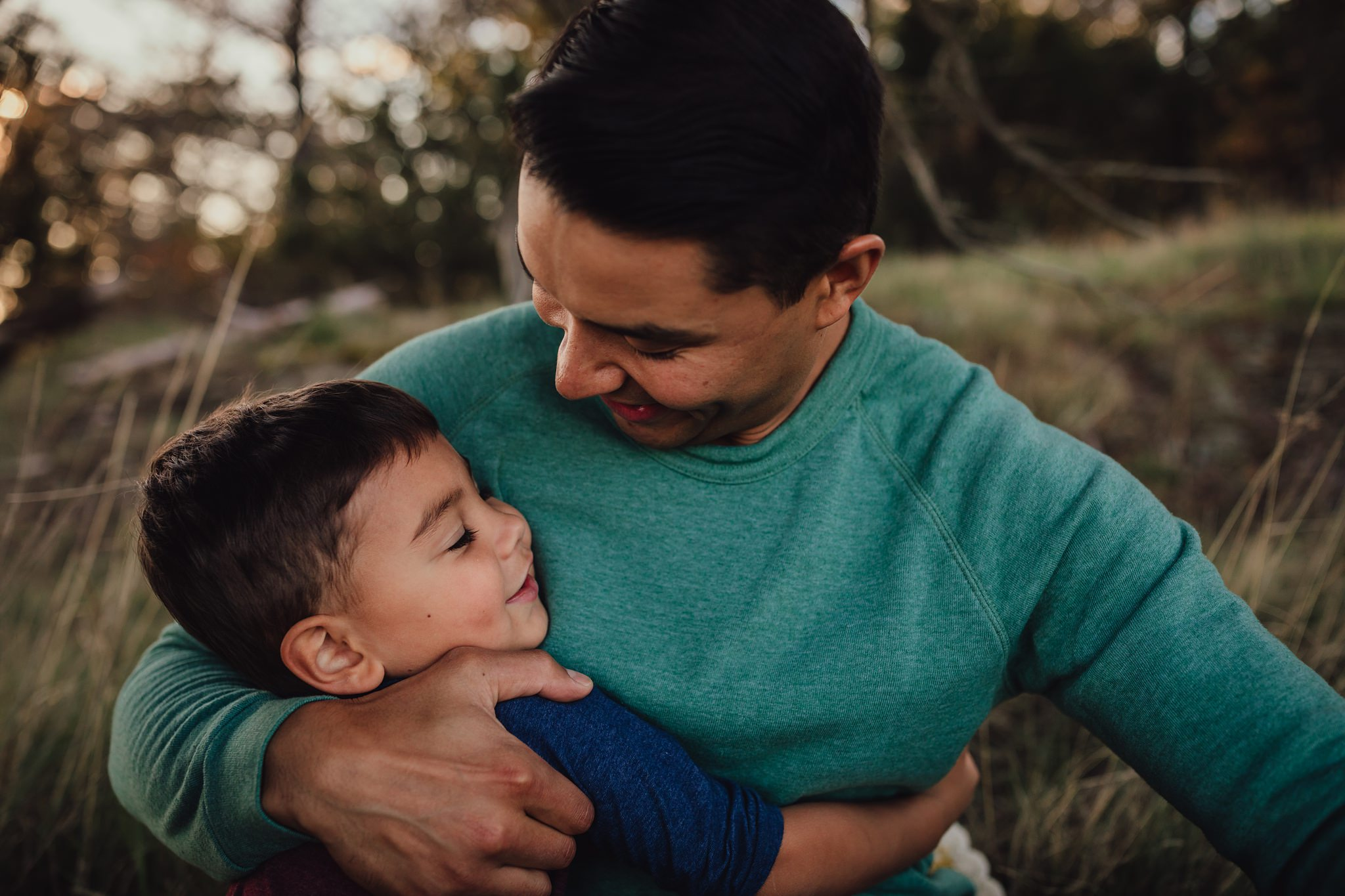 father hugs son during family photo session