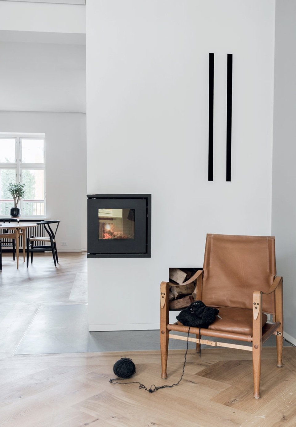In a warm corner in front of the fireplace stands a Kaare Klint Safari Chair.