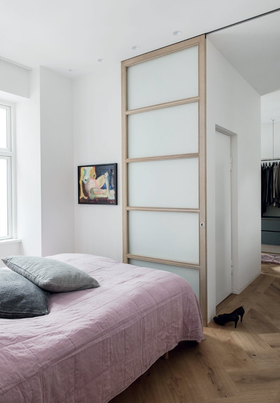 A sliding door in light ash wood glides over herringbone parquet floor, and with the absence of a doorstep lends to a minimalist Japanese feeling to lift the boundaries between rooms.