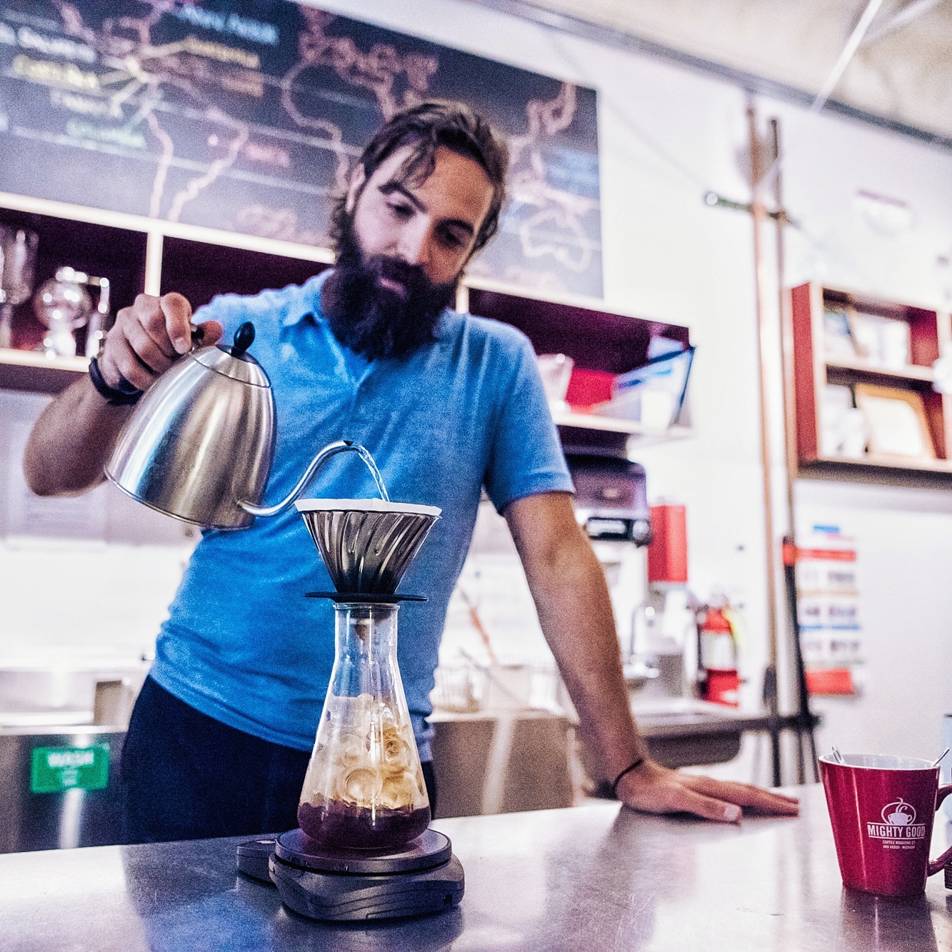 A man makes an iced pourover while leaning on the counter