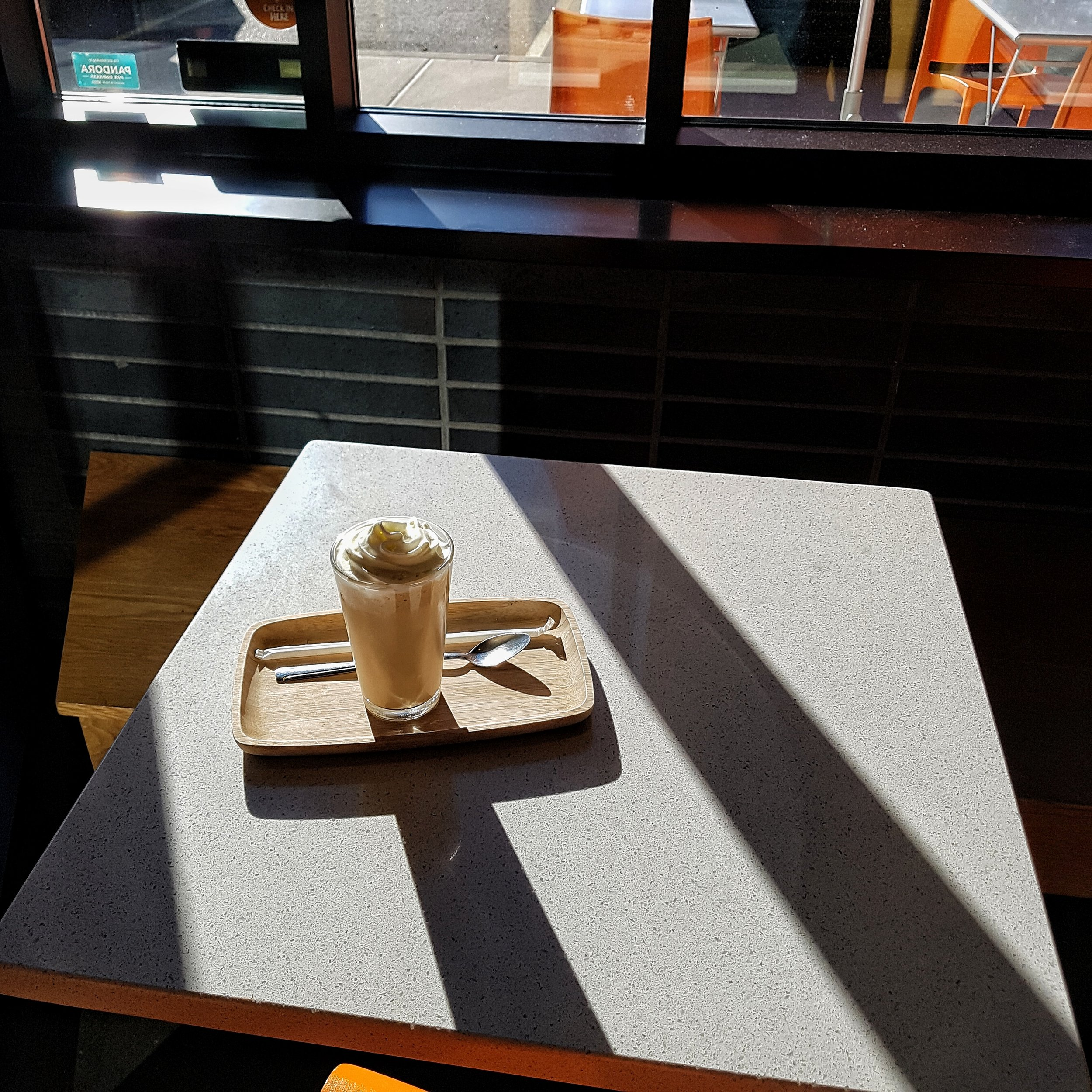 A milkshake sits on a table in the sun