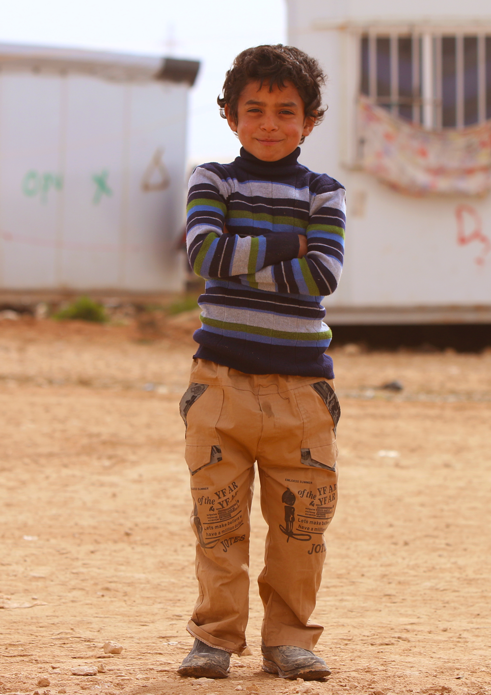 Syrian refugee boy crossing arms