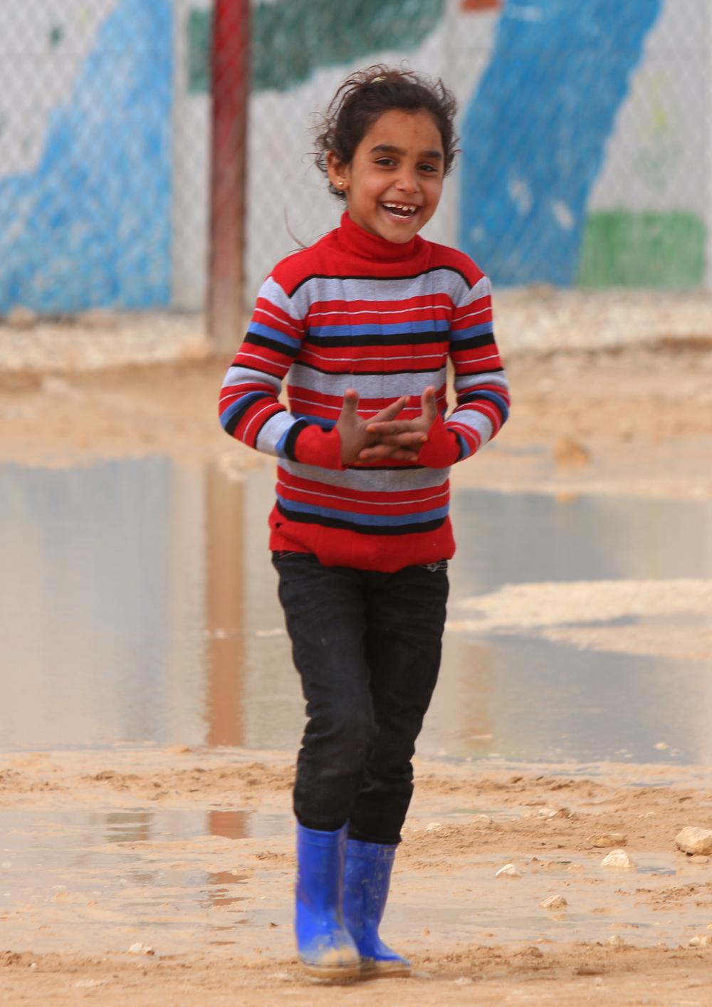 Syrian refugee smiling girl walking