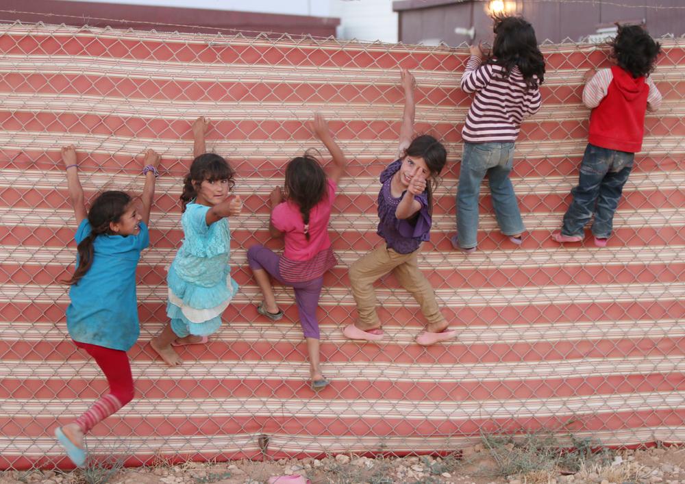 Refugee camp children climb fence