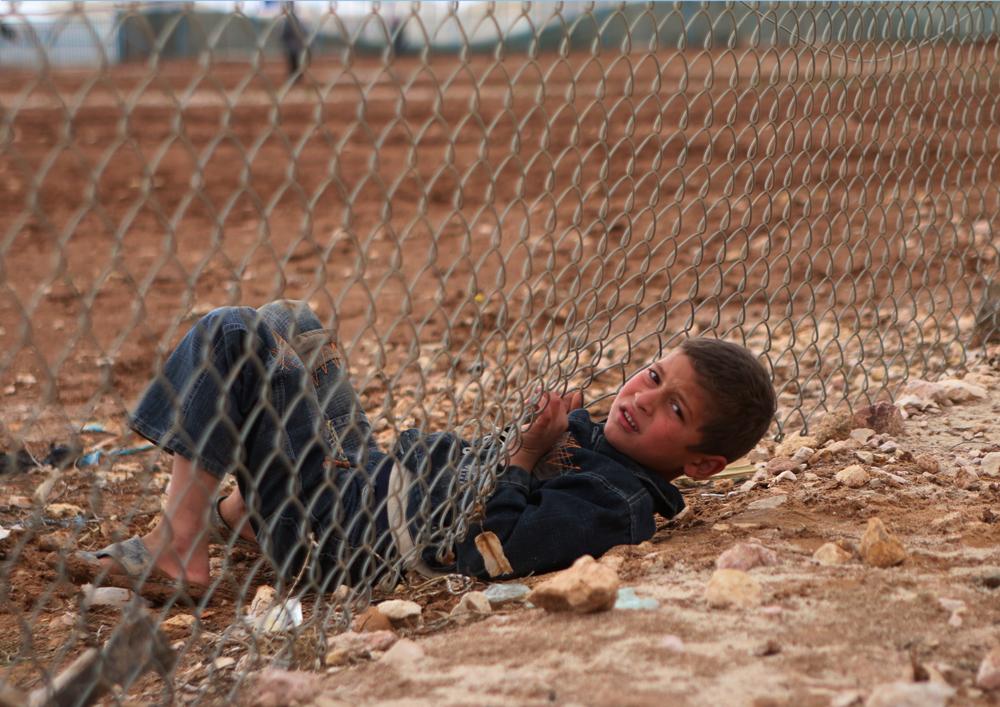 Syrian boy under fence in refugee camp