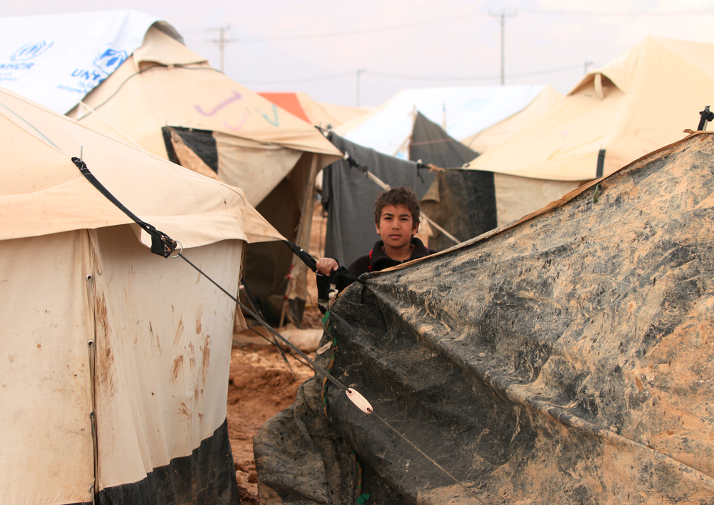 Syrian child among refugee camp tent