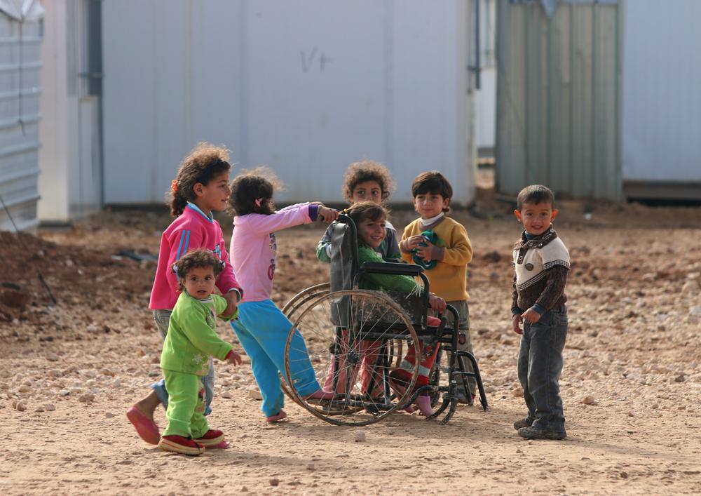Injured syrian children play in refugee camp