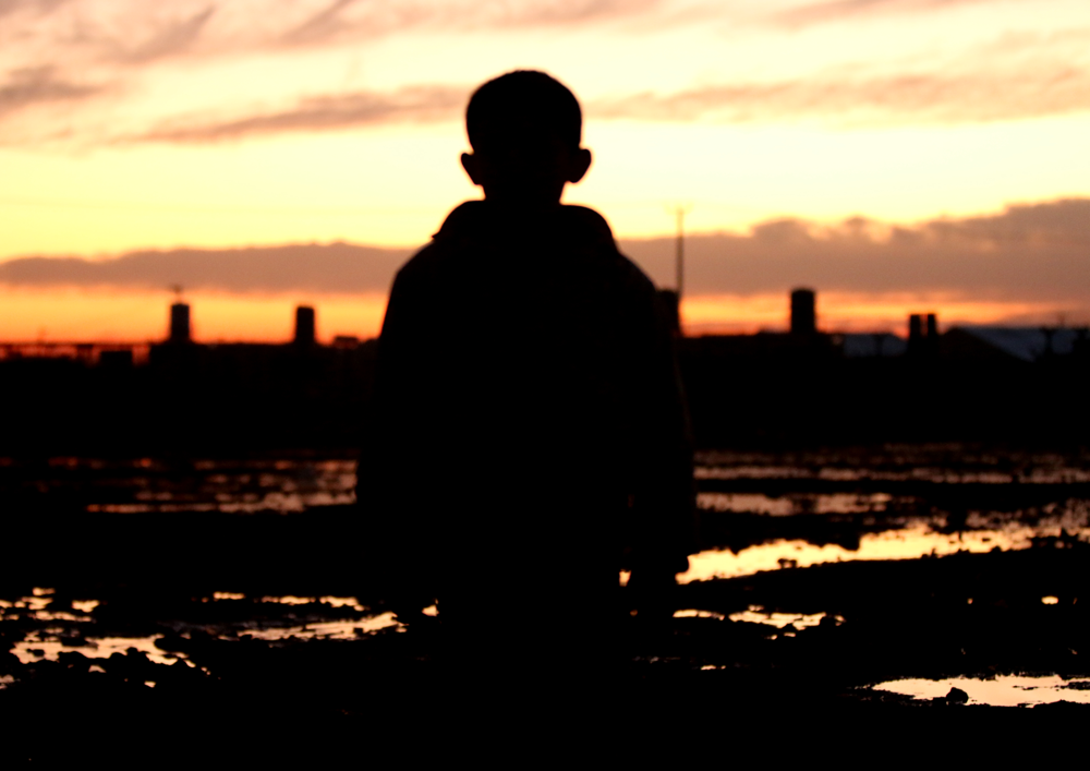 Syrian child in sunset refugee camp