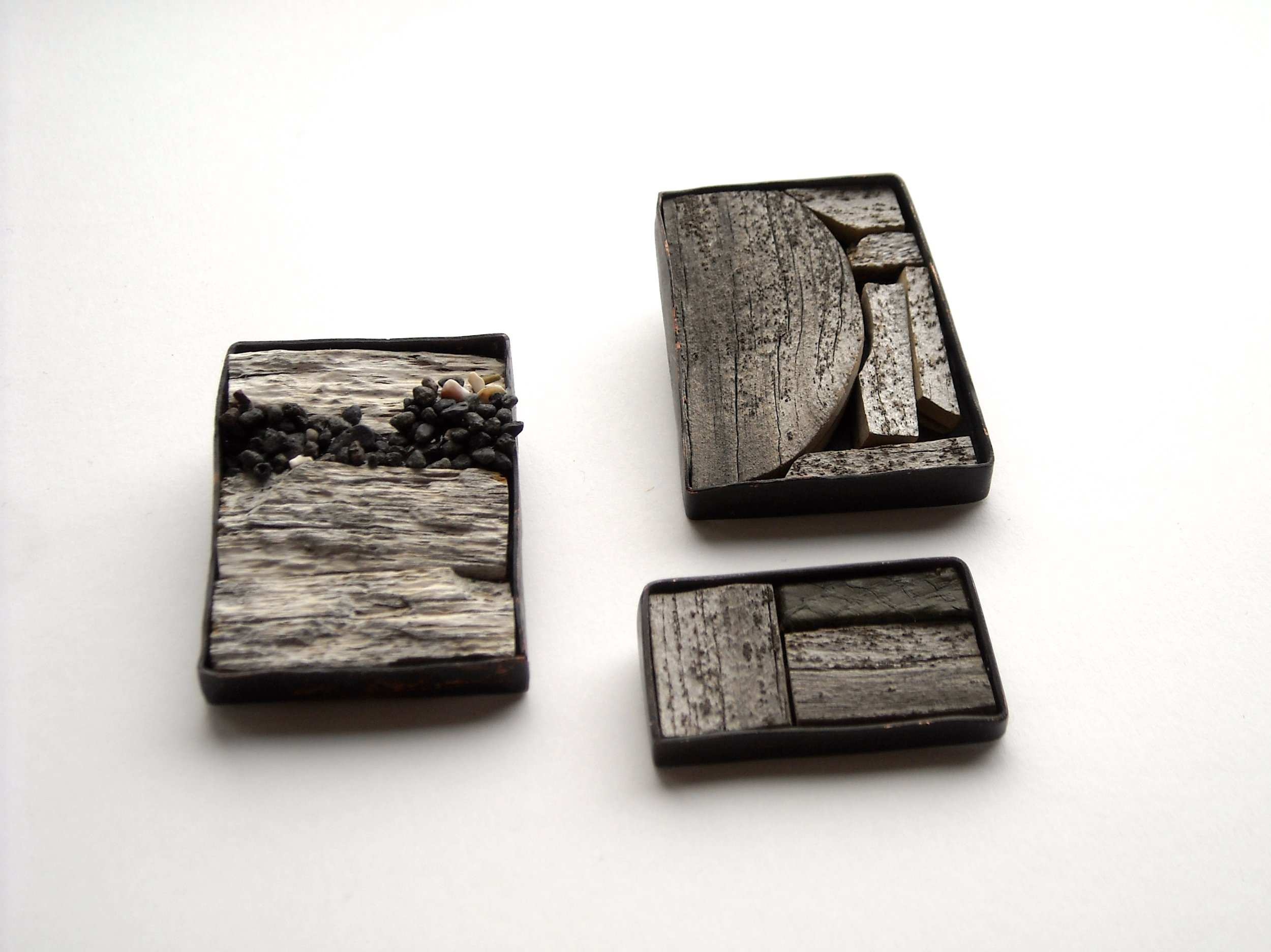Brooches. Copper, driftwood, lava.