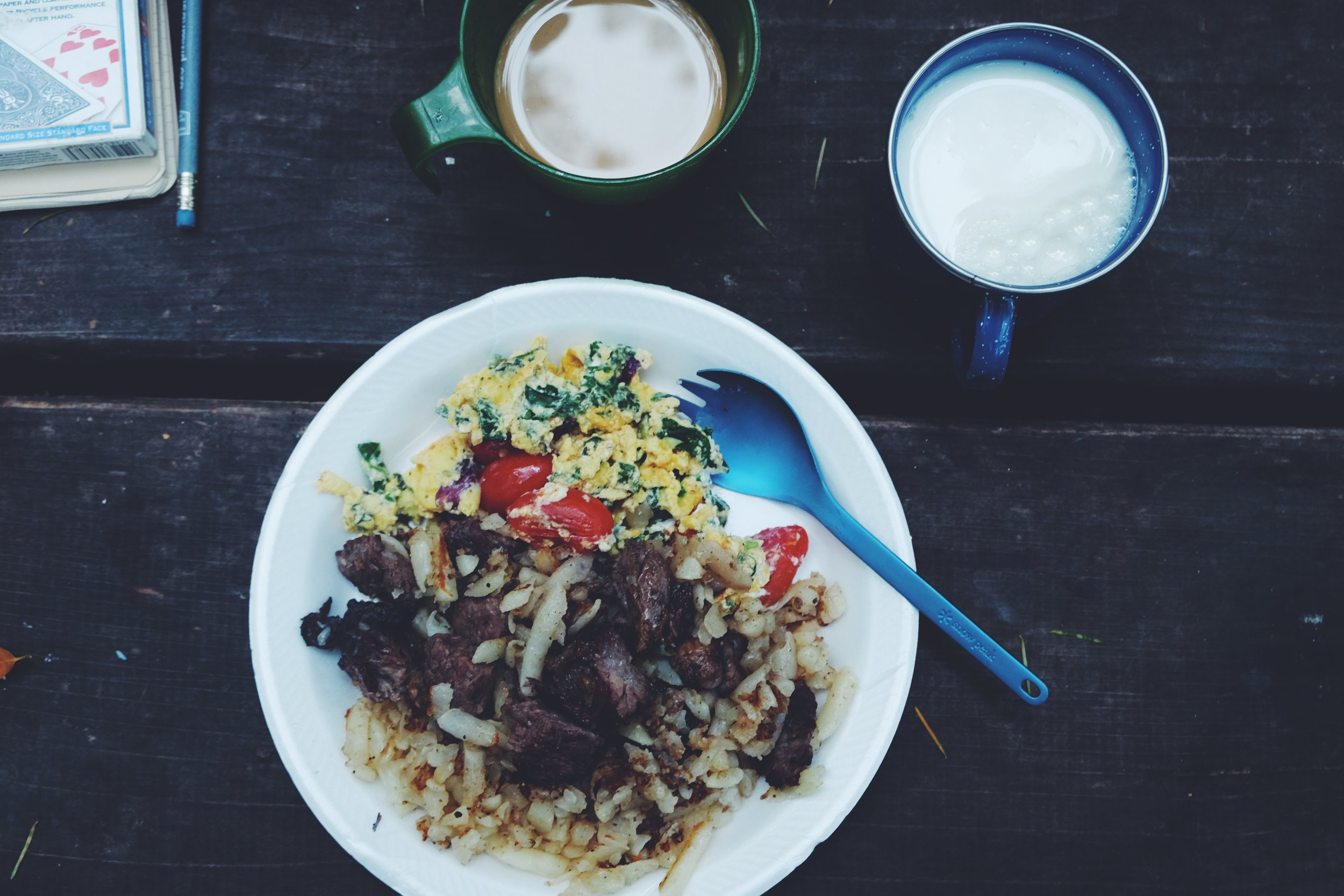 Megameals are important when camping..even if I cant eat it all.  Here we have hash browns, eggs whites with goat cheese + kale + cherry tomatoes, and left over ribeye steak from the night before.  Coffee and milk to compliment the buds.  #MikeDsKitchen