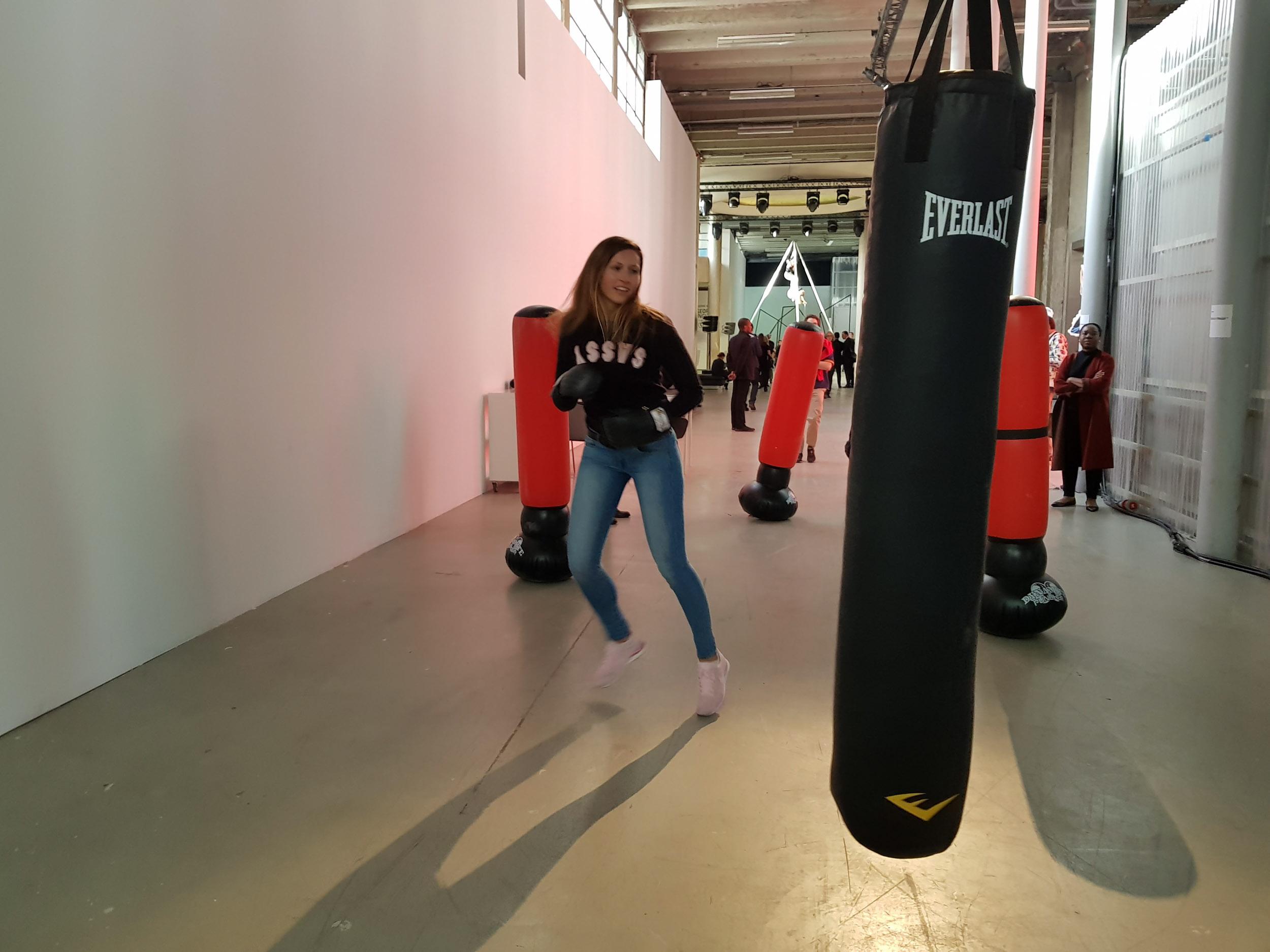 Female athletes of MMA (Mixed Martial Arts, a hybrid combat sport also known as «free-fight» or «ultimate fighting») perform free-fight movements on the punching bags.  The role-playing rule of the installation is that only women are allowed to physically interact with it: they can borrow gloves, touch/hit the punching bags, or use the markers to write on them.  The behavior and interactions of the visitors creates something between a social psychology experiment and a non-linear play.