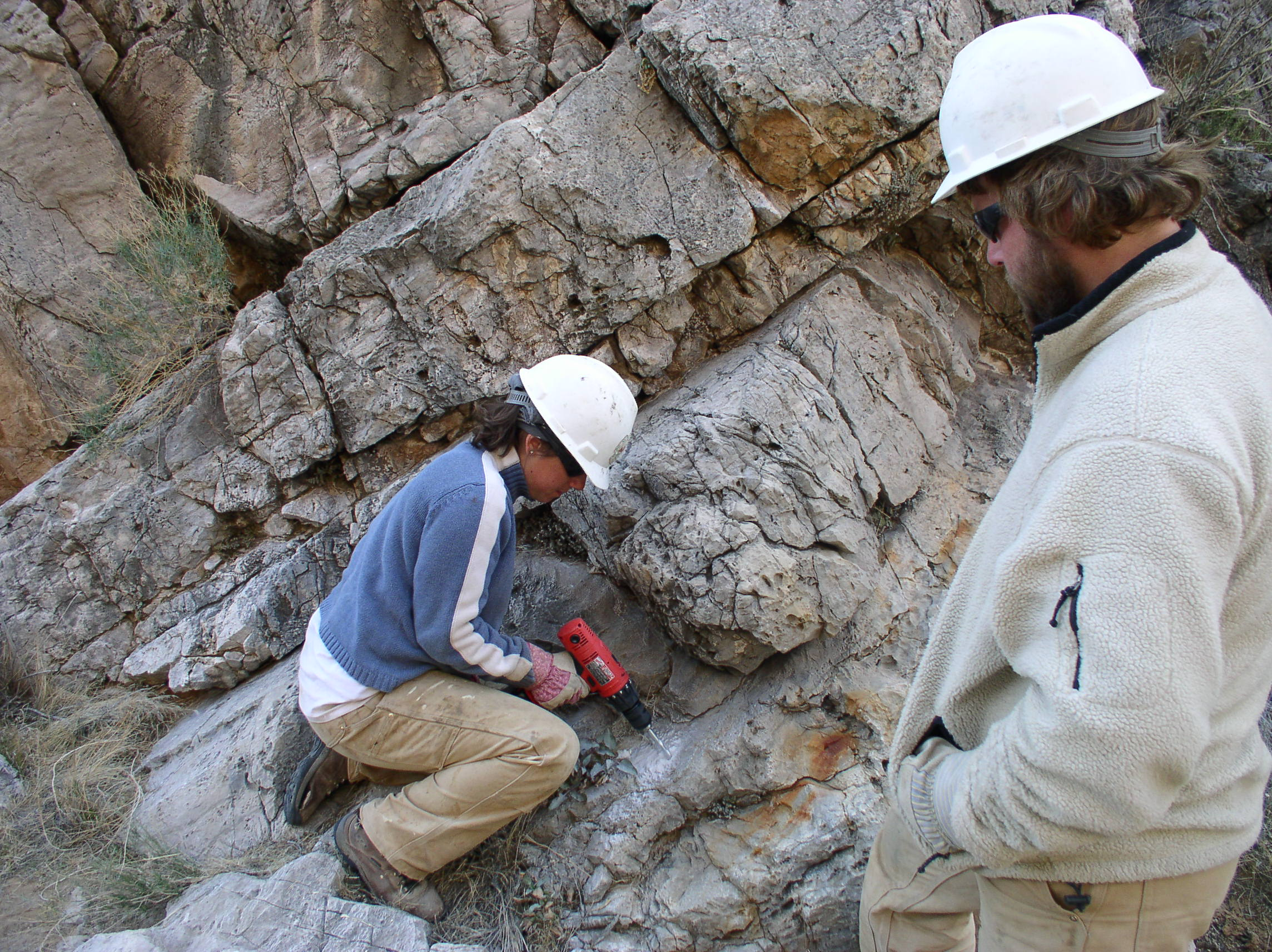 Drilling into rocks to build a fence to prevent ATVs from driving down a canyon.