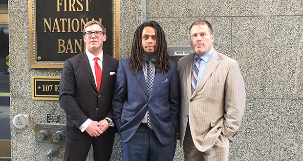Christopher Lollie (center) stands with attorneys Andrew Irlbeck (left) and Paul Applebaum at the the First National Bank Building in St. Paul. A lawsuit over Lollie's arrest in the skyway of that building cost the city of St. Paul $100,000.
