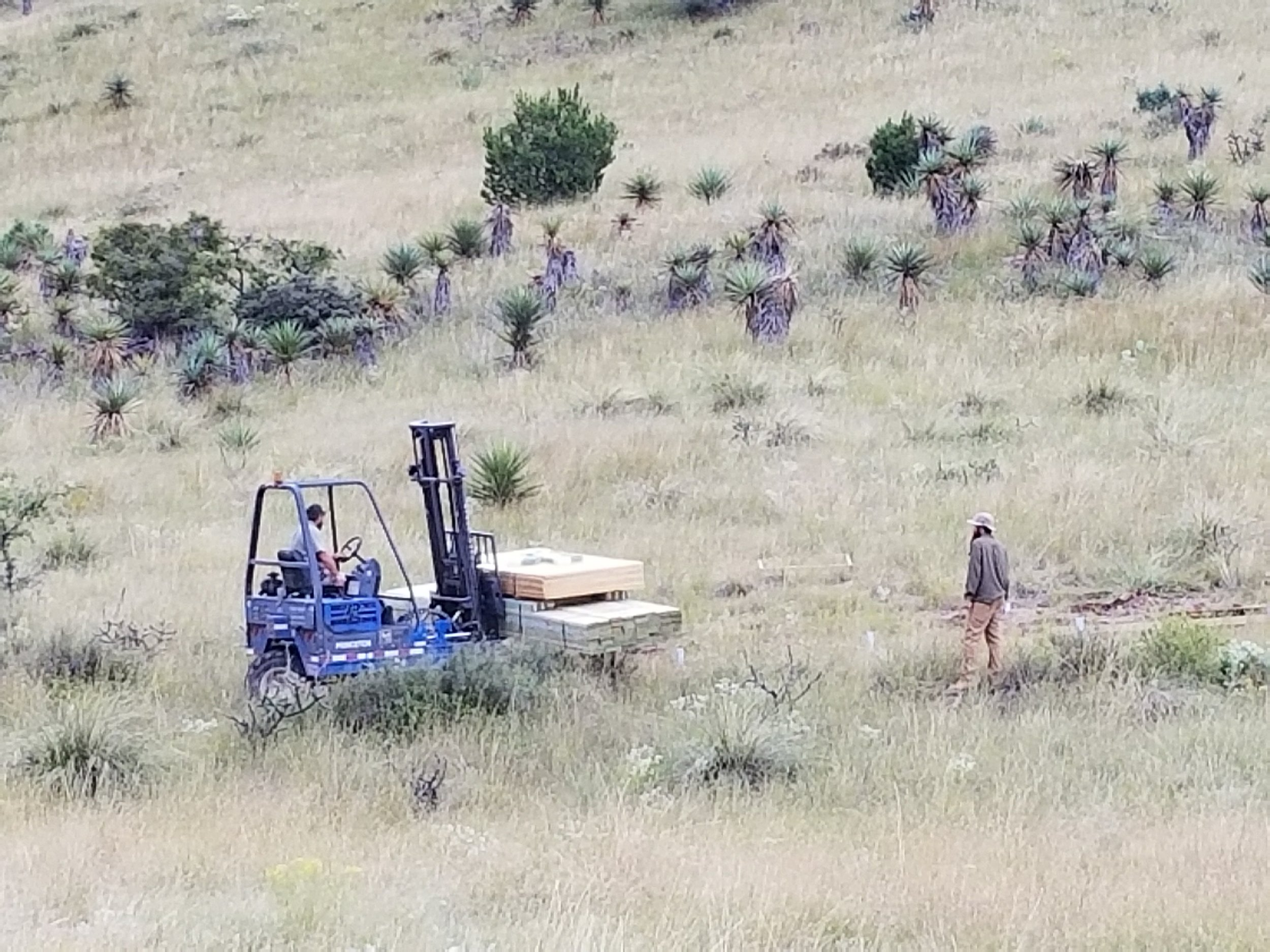 Off-road forklift taking the wood up to the tent spot.