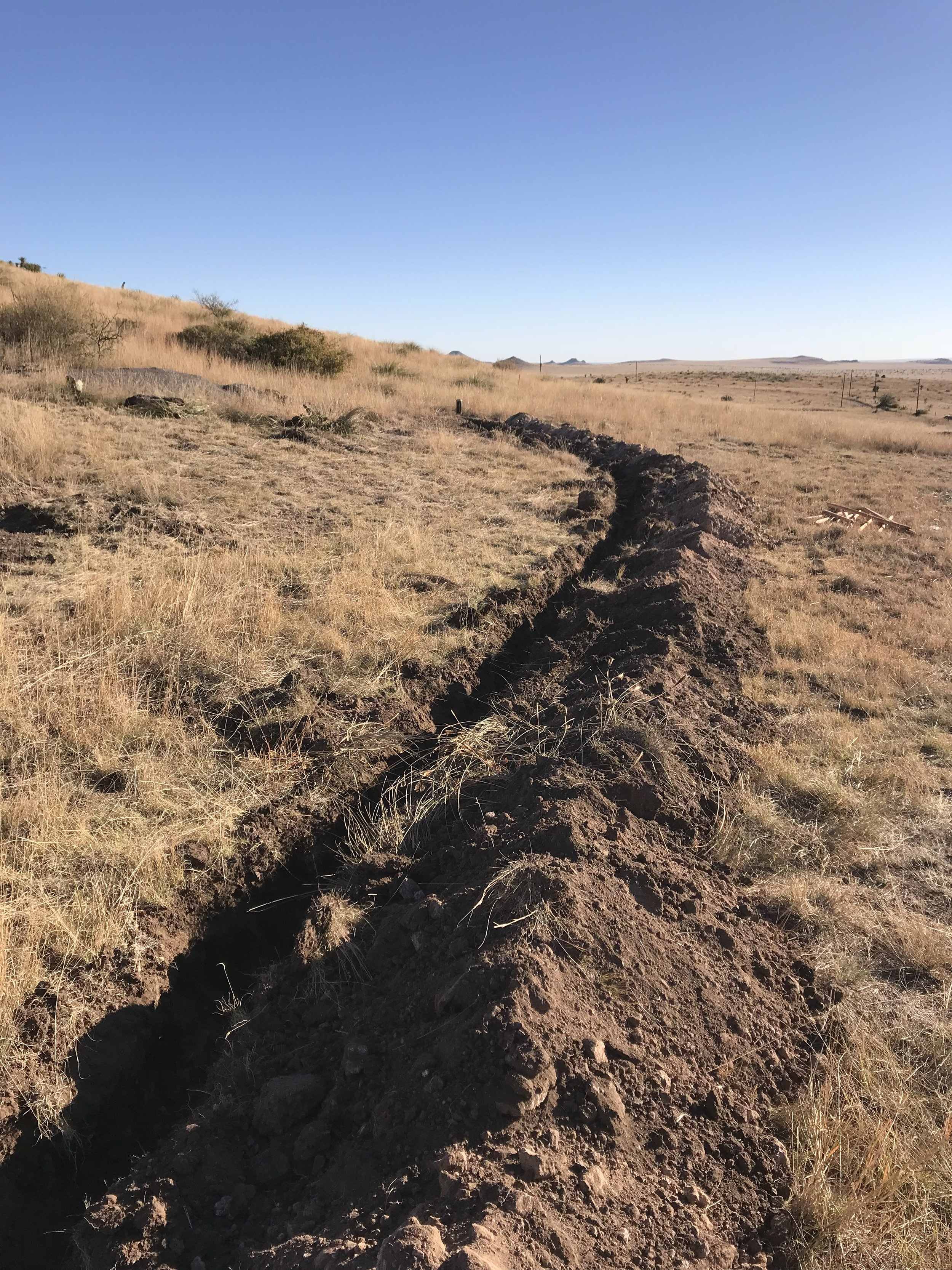 This ditch will hold a pipe carrying water from the well to the new water storage tank.