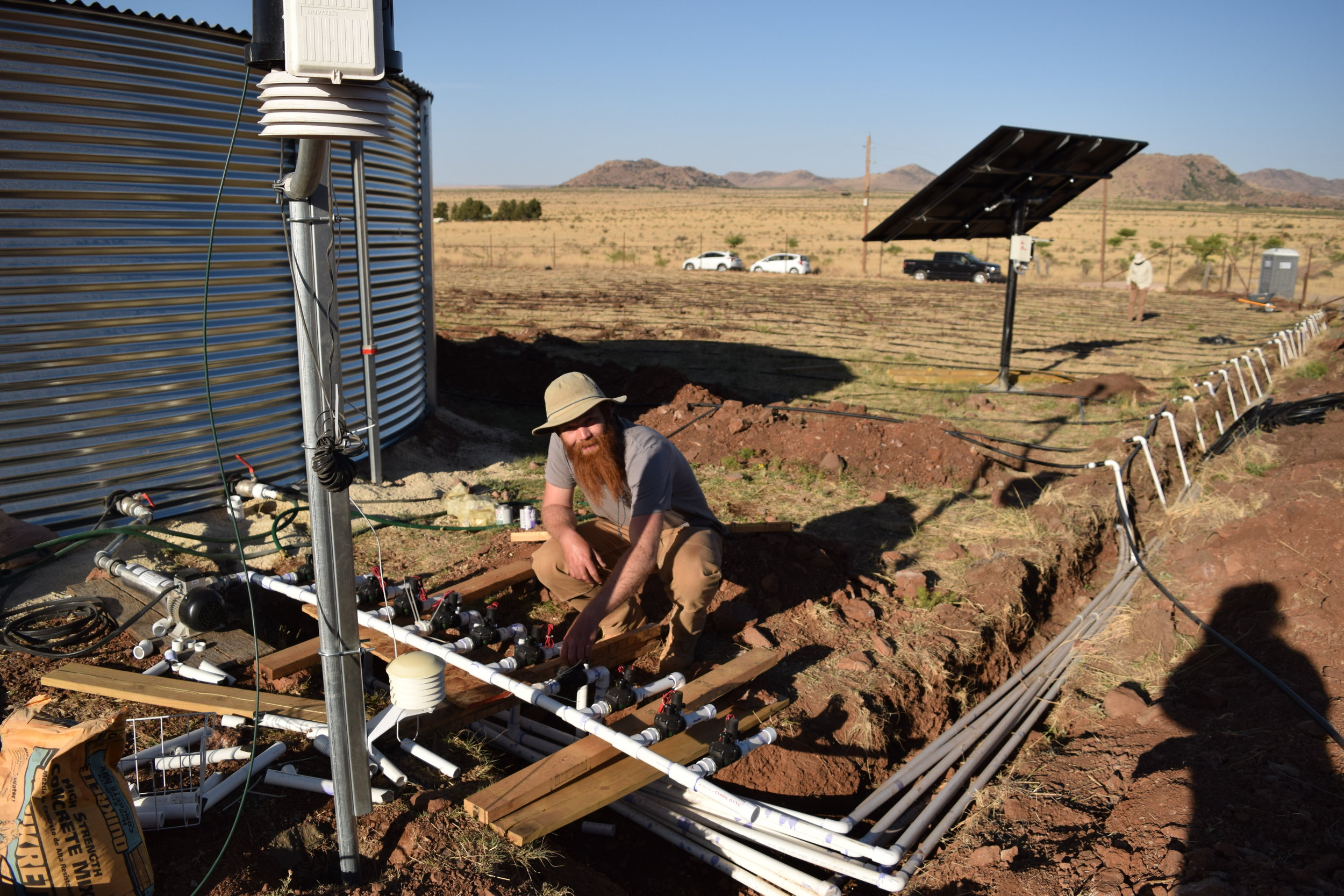 Here you can see all the pieces of the irrigation system except the well. Water flows from the silver storage tank through the solar powered irrigation pump, through the valve manifold, which is controlled by the irrigation controller, then is sent to any of 7 irrigation zones through the PVC pipes and into the drip tubing,