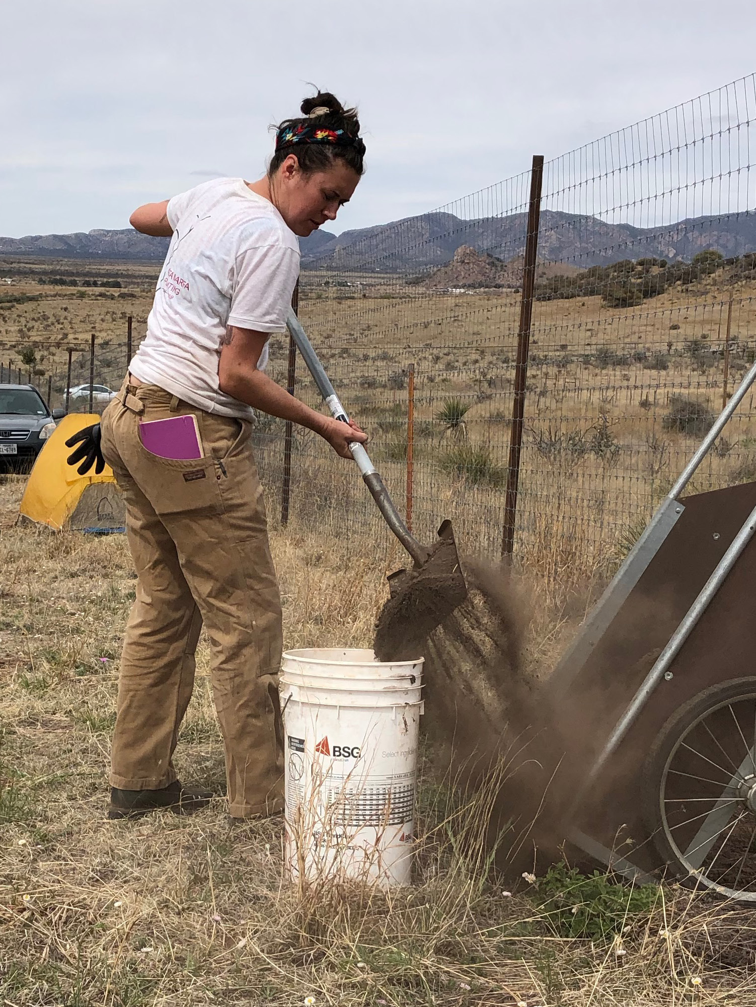 Katie filling up the dirt bucket to bring dirt to the rocky area at the top of the hill.