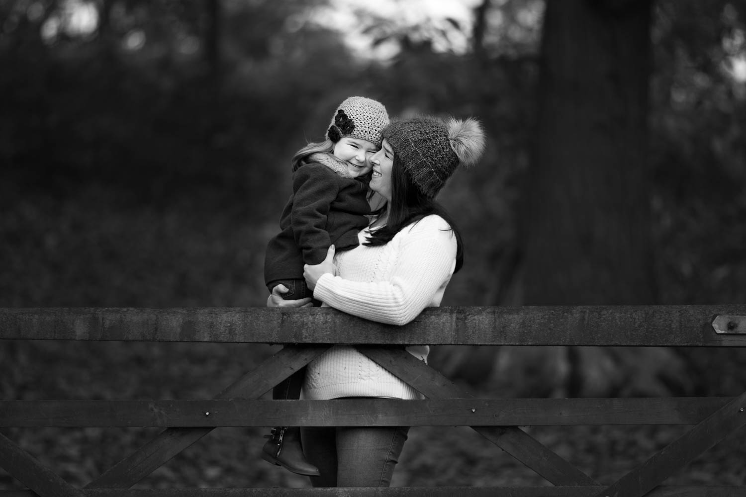 Mother and dughter posing against a gate during an Autumn family photoshoot at Ampthill Park in Bedford.