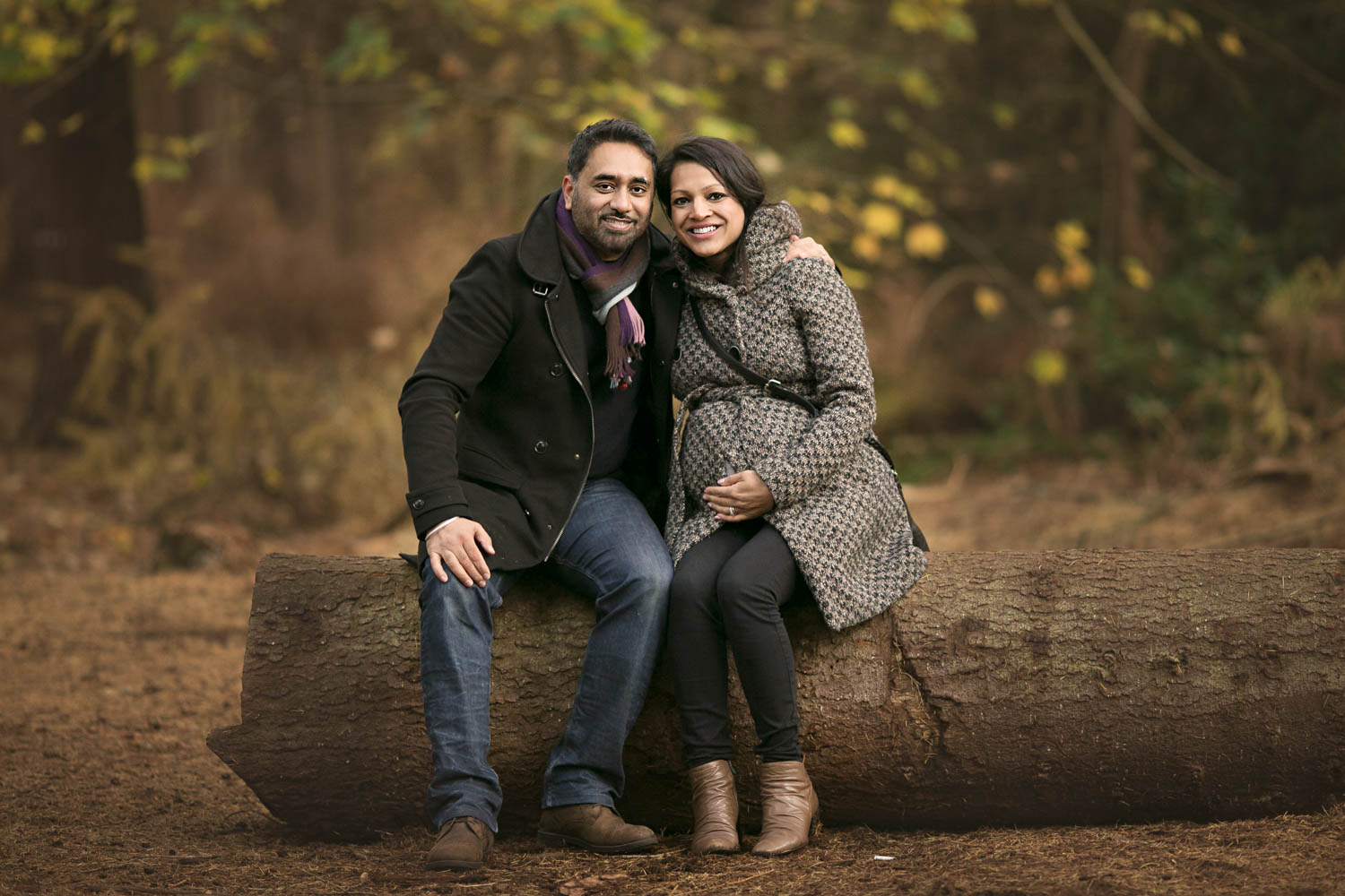 Couple posing on a log during an Autumn photoshoot in Rushmere Park on the Bedfordshire and Buckinghamshire border.