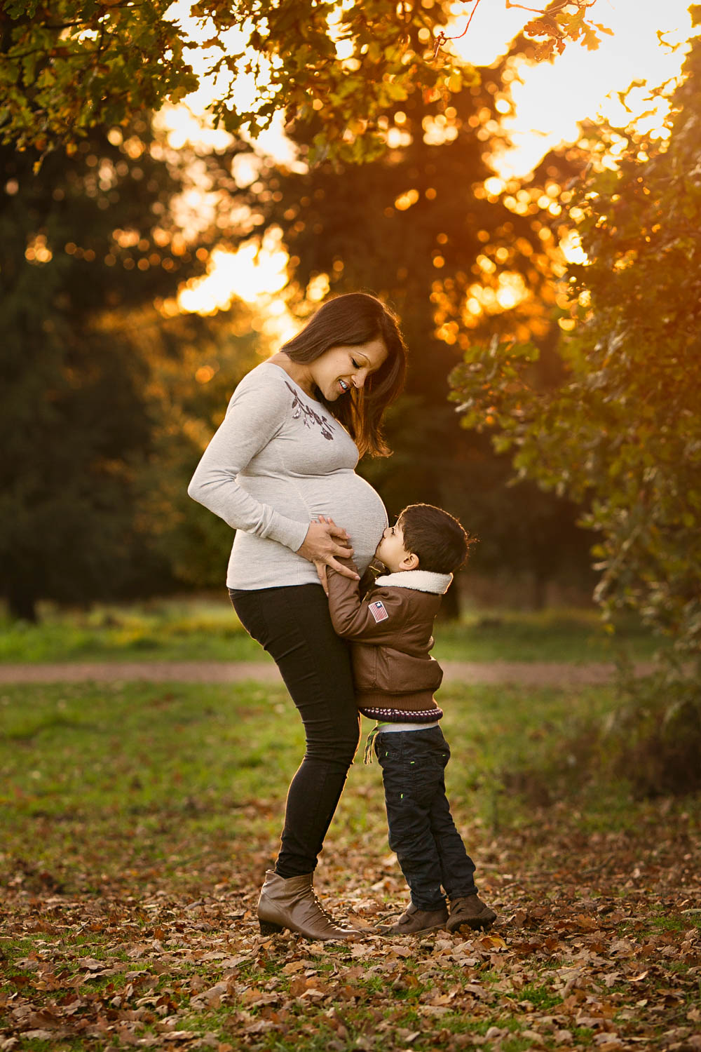 Pregnant mother and son kissing bump during a Family Autumn photoshoot at Rushmere park in Bedfordshire.