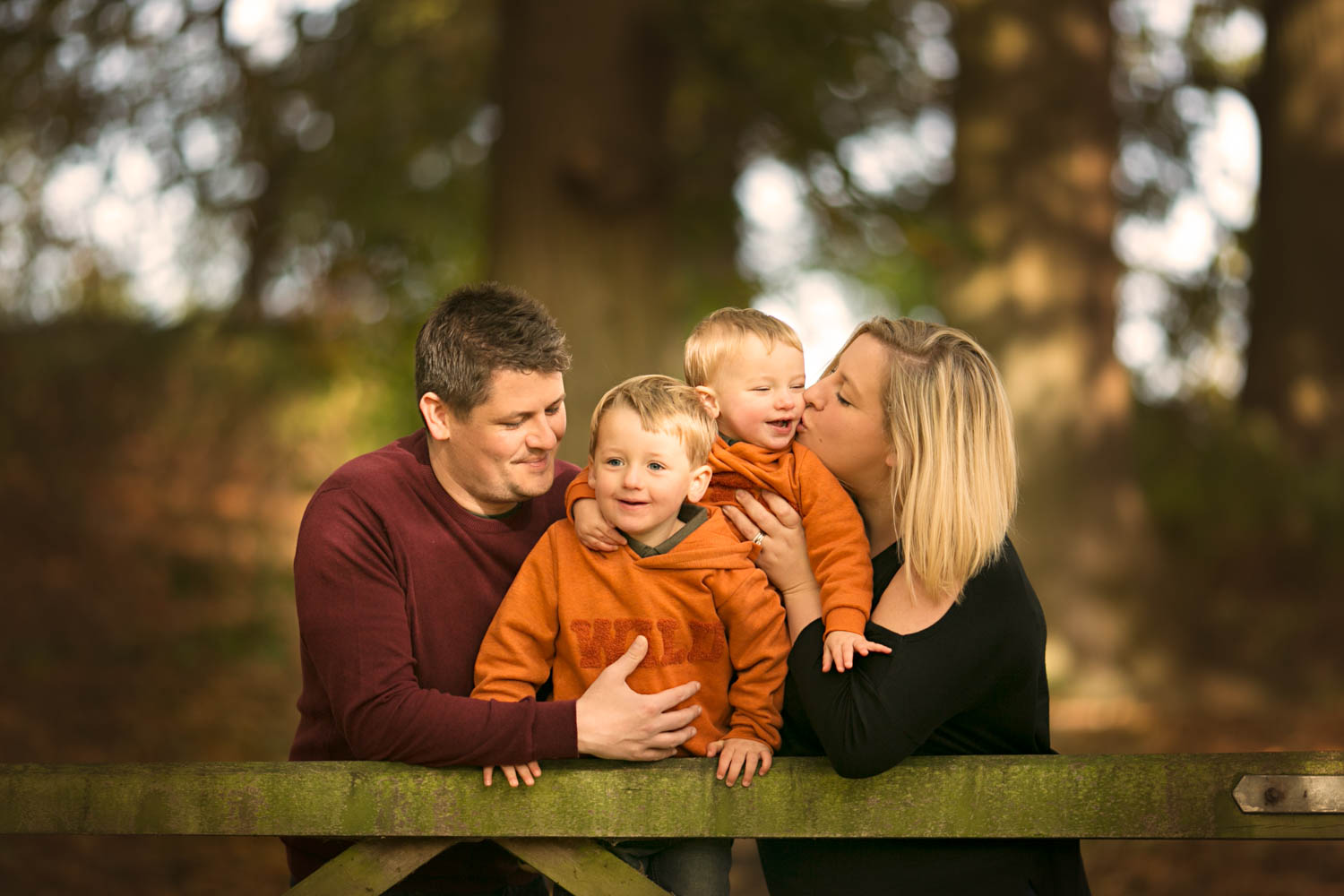 Family posing againgst a gate with mum kissing son during an Autumn family portrait session at Ampthill Park in Bedford.