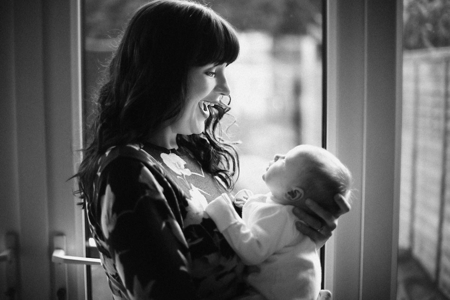 Black and White image of Mother and Newborn naturally posing in front of window during baby lifestyle photoshoot at clients home in Bedford.