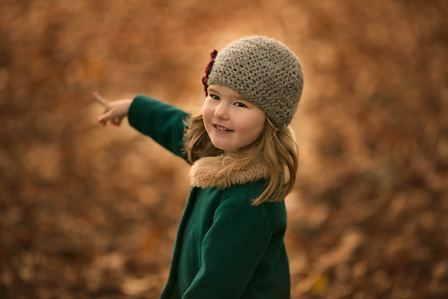 Little girl pointing, against beautiful autumn colours during family photoshoot at Ampthill Park in Bedford.