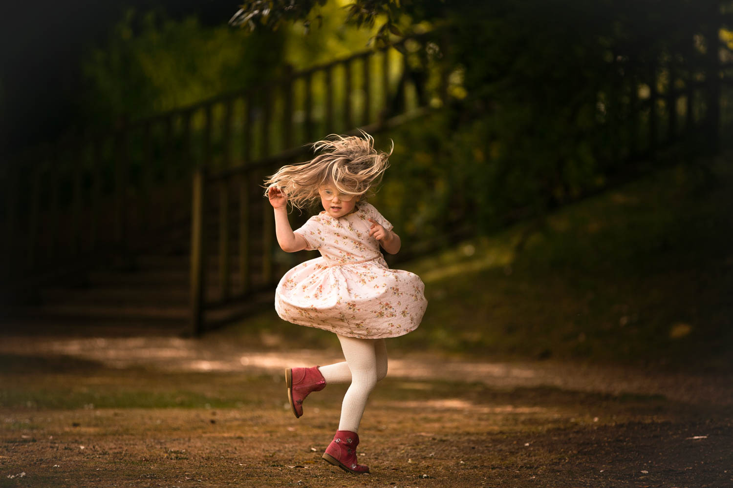little girl spinning during child photography session at Castle Ashby, Northampton.