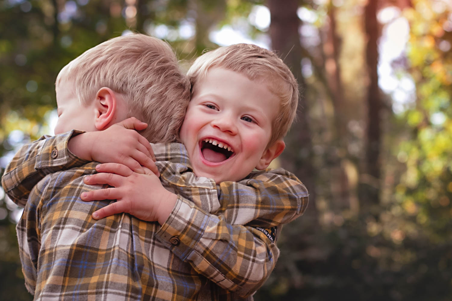 Twin brothers hugging in family portrait during an autumn family photoshoot in Bedford.