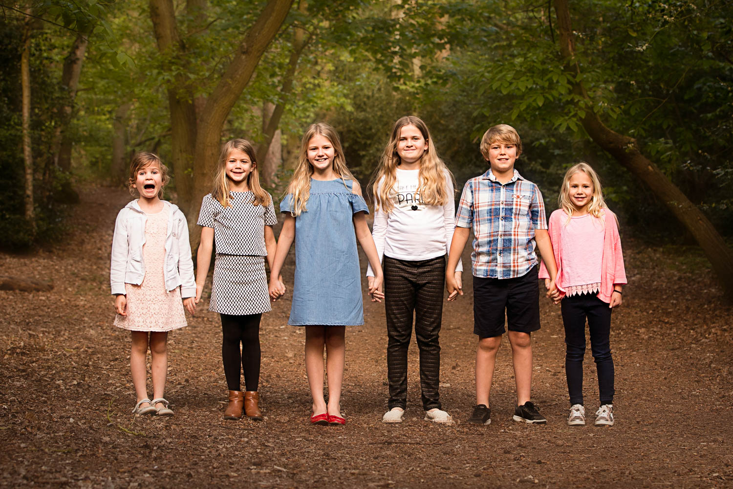 Siblings and cousins line up for family portait during Autumn photoshoot at Ampthill Park, Bedford.