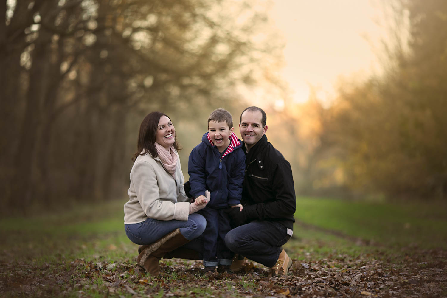 Mother, father and son posing for a family portrait in the golden hour on a autumn photoshoot in Milton Keynes.