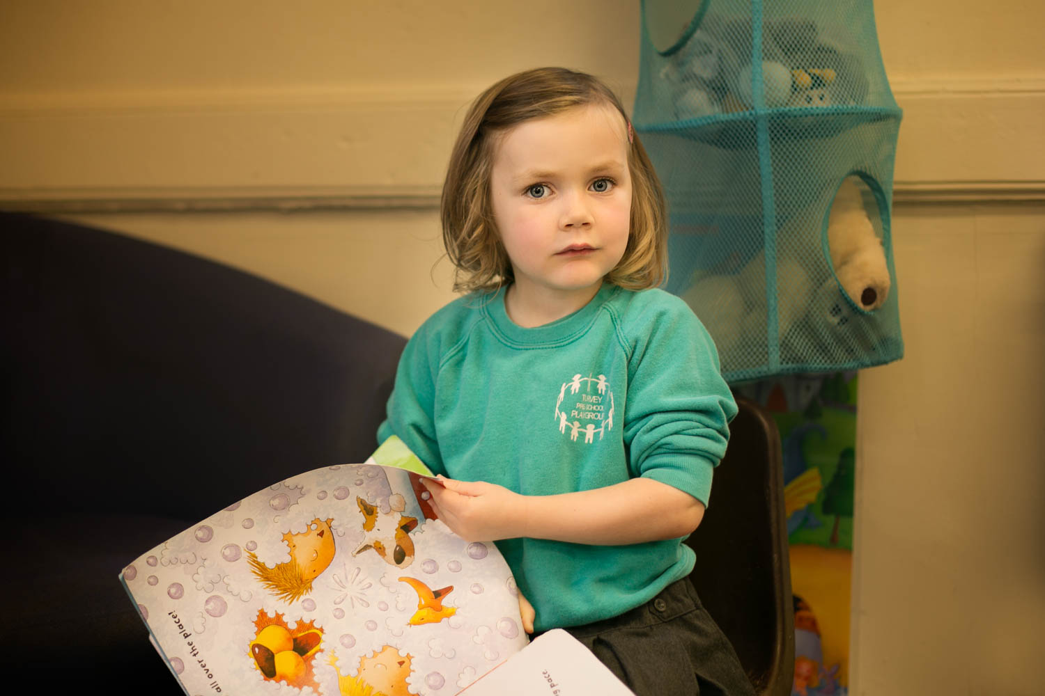 Girl reading a book during preschool photoshoot in Turvey Bedford.