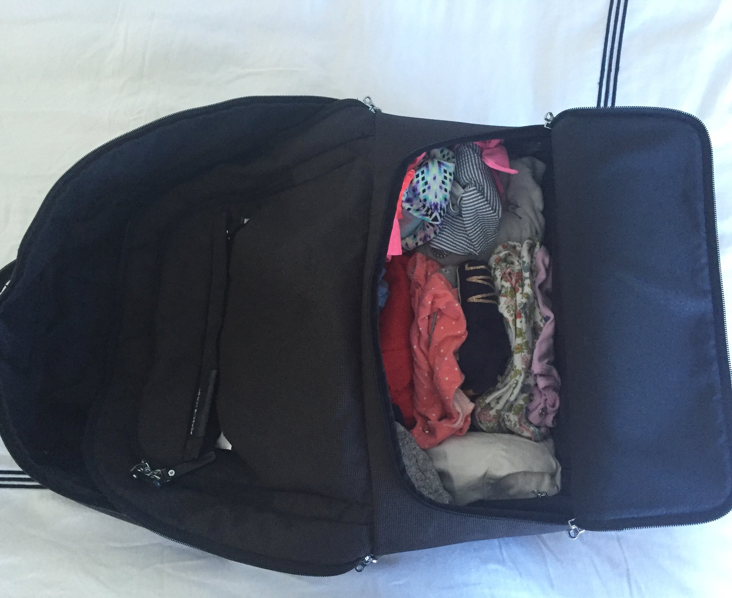 First Layer - Baby gets the smaller side of the suitcase. Roll outfits tight and put them in rows. Keep extra onesies/socks/bibs at the edge.
