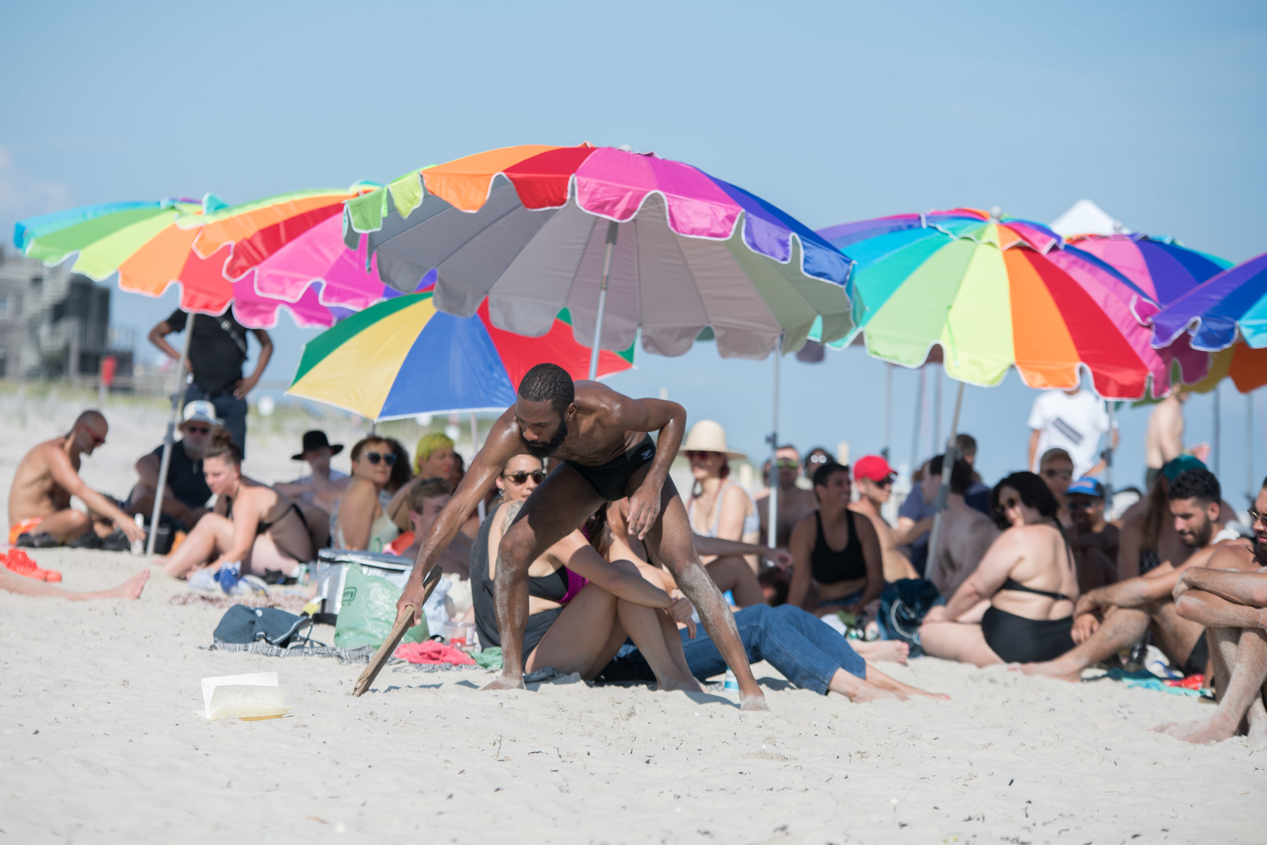 I crouch down and write in the sand with a large wooden stick. The audience sits behind me under an arrangement of colorful beach towels. Photo by Nir Arieli
